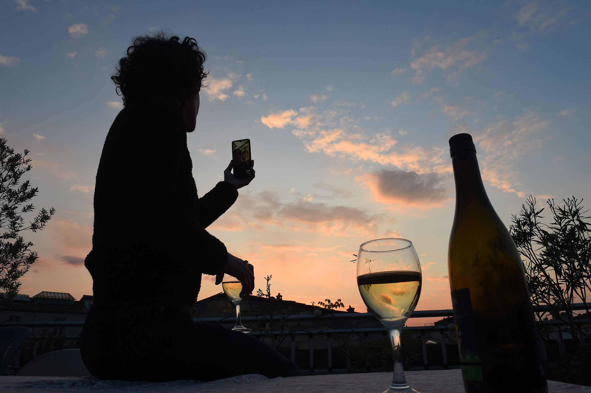 A woman drinks a glass of wine as she speaks and shares a drink with friends via a video call on March 26 in Bordeaux, southwestern France, in the evening on the tenth day of a lockdown aimed at curbing the spread of the COVID-19 in France
