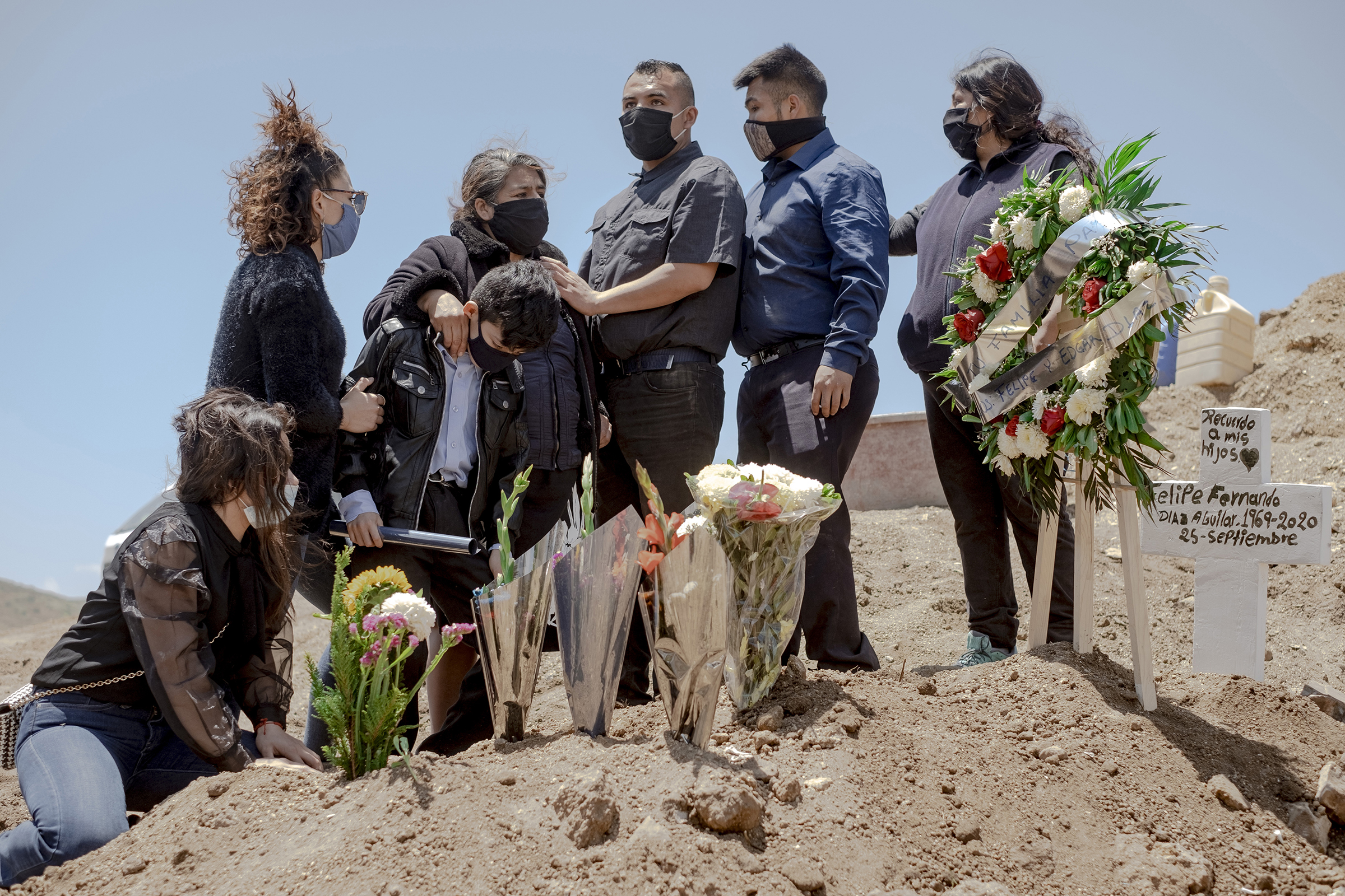 A family wearing protective masks mourns during the burial of a relative who died from coronavirus at Municipal Cemetery No. 13 in Tijuana, Mexico, on May 12.