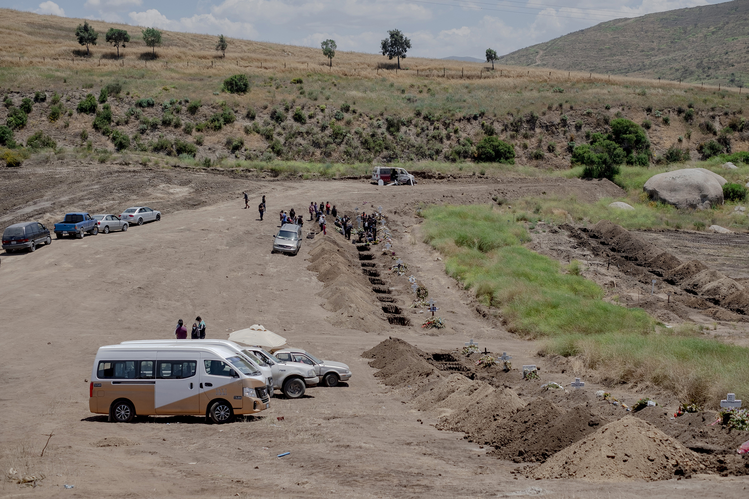 A burial at a newly dug grave at the Municipal Cemetery No. 13 in Tijuana, Mexico, on May 12. Experts say Mexico's COVID-19 case count and death toll have been underreported.