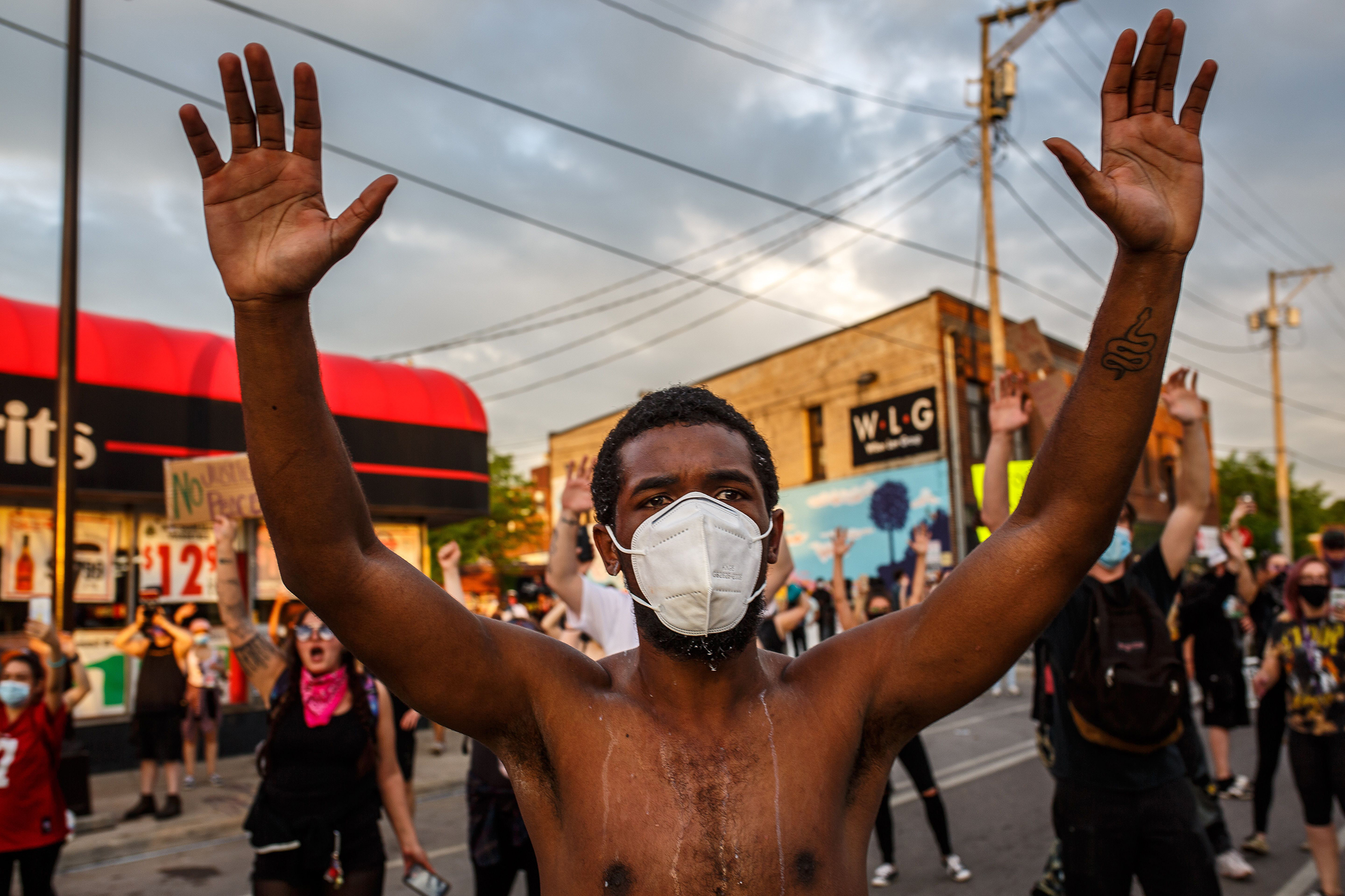 A protester wearing a mask holds up his hands during a demonstration outside the 3rd precinct on May 27.