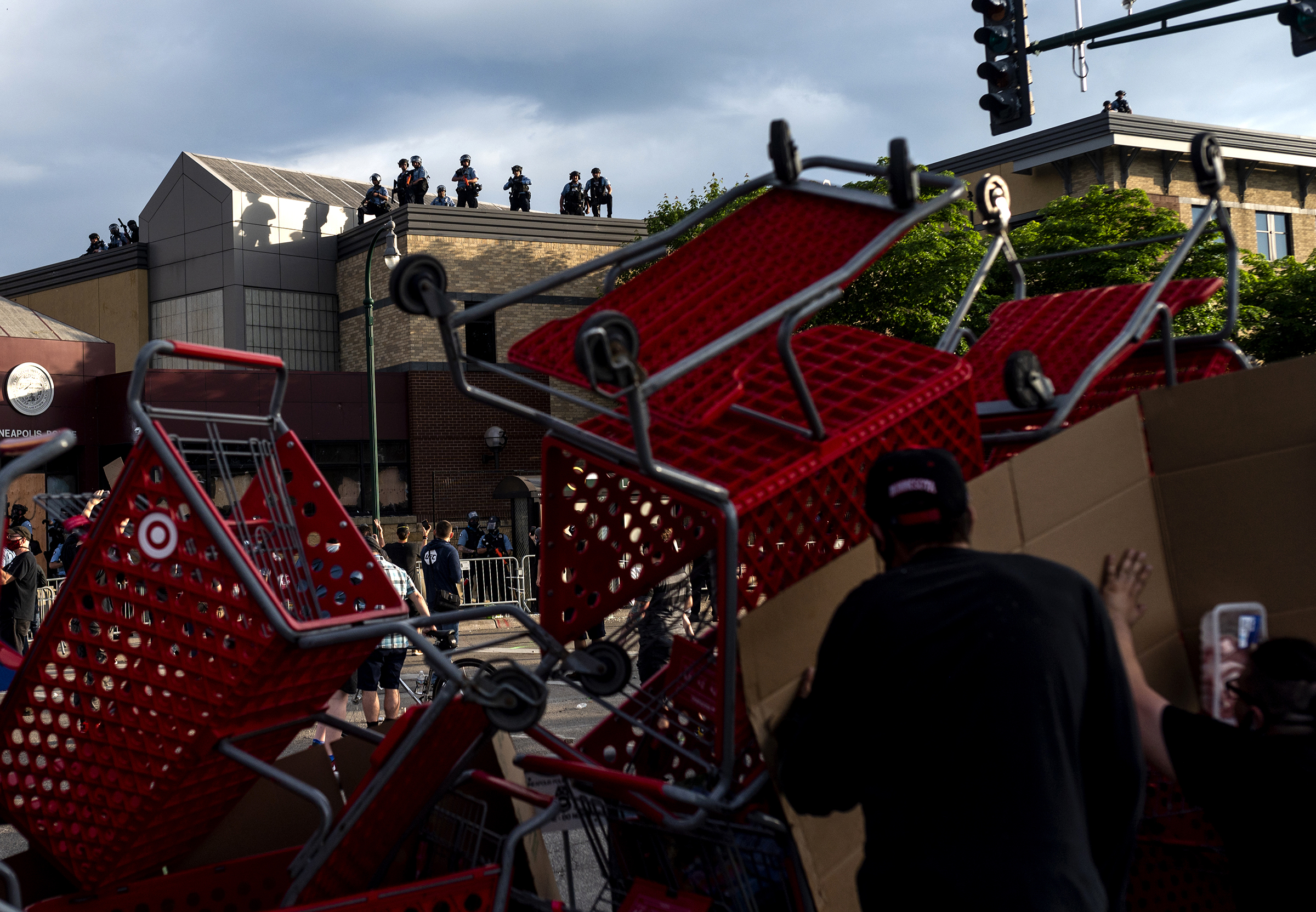 Protesters use shopping carts as a barricade as they confront police near the 3rd precinct on May 27.