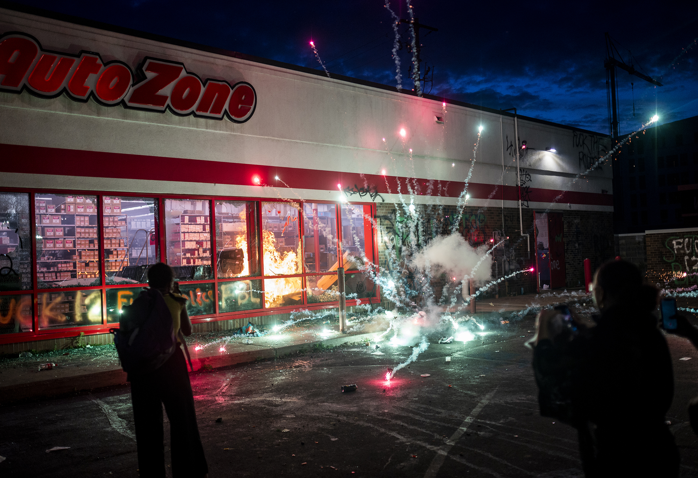 A firework explodes as a fire burns inside of an Auto Zone store near the 3rd precinct in Minneapolis on May 27.
