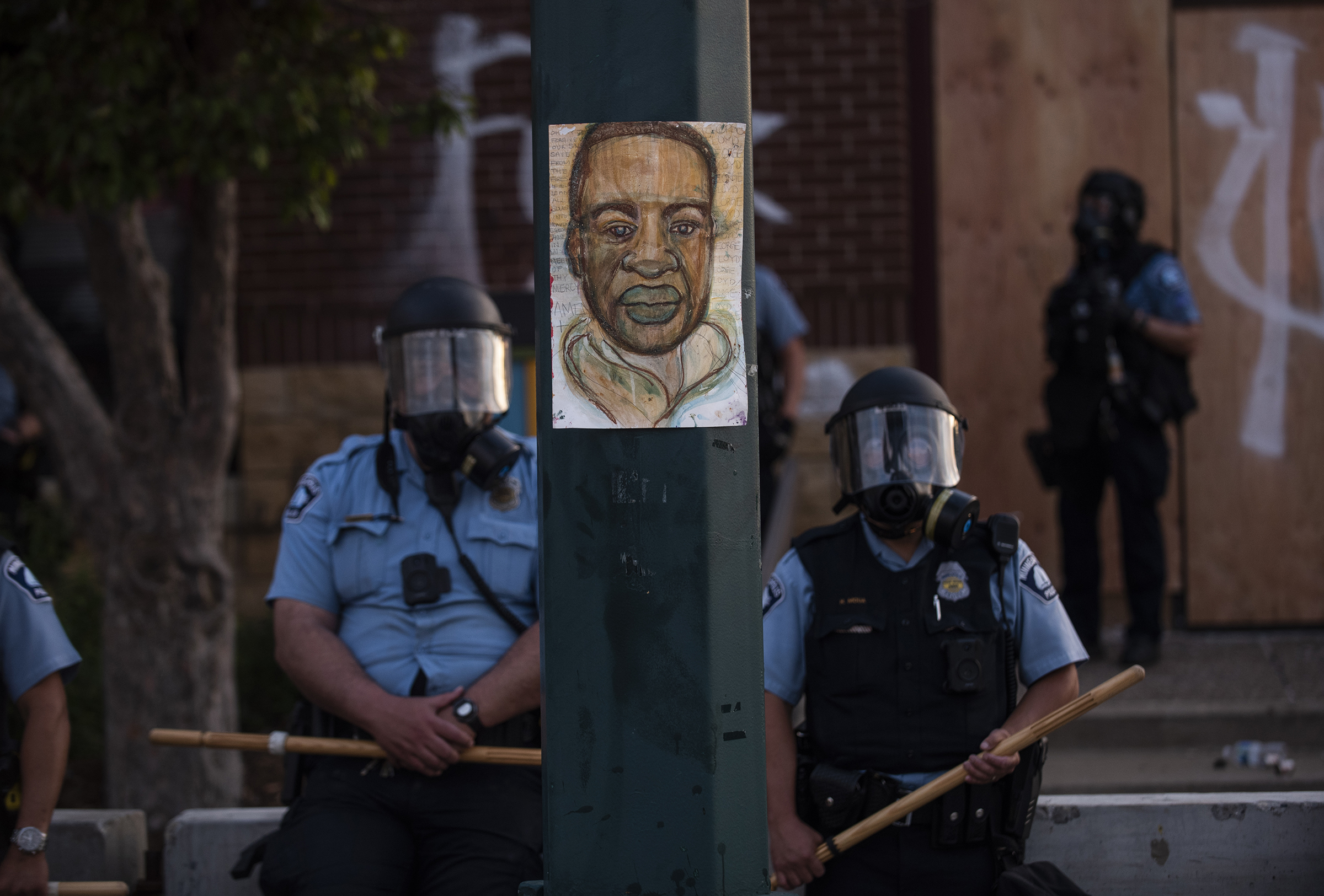 A portrait of George Floyd hangs on a street light pole as police officers stand guard at the 3rd precinct during a face off with protesters on May 27.