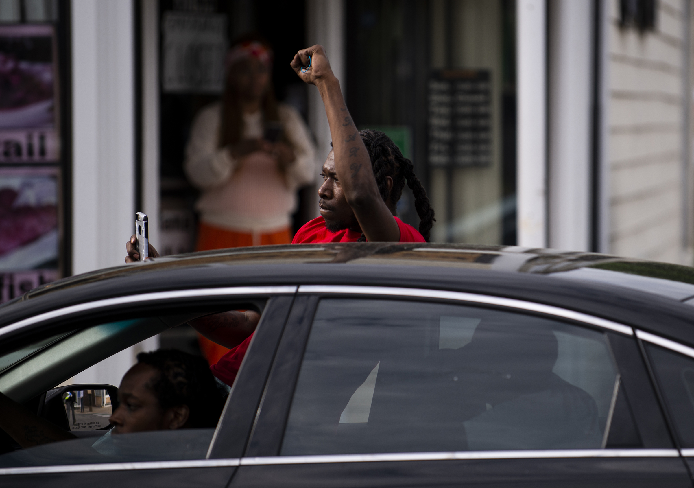 A man leans out of his car and with a raised fist as protesters march by decrying the killing of George Floyd in Minneapolis on May 26.