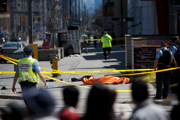 A tarp lays on top of a body on Yonge St. at Finch Ave. after a van plowed into pedestrians on April 23, 2018 in Toronto, Canada.