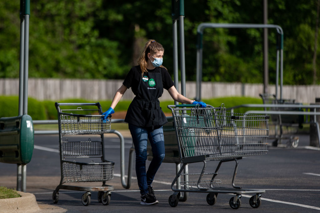 A worker wearing a protective mask pushes shopping carts at a Whole Foods Market Inc. store in Birmingham, Alabama, U.S., on Tuesday, April 28, 2020.
