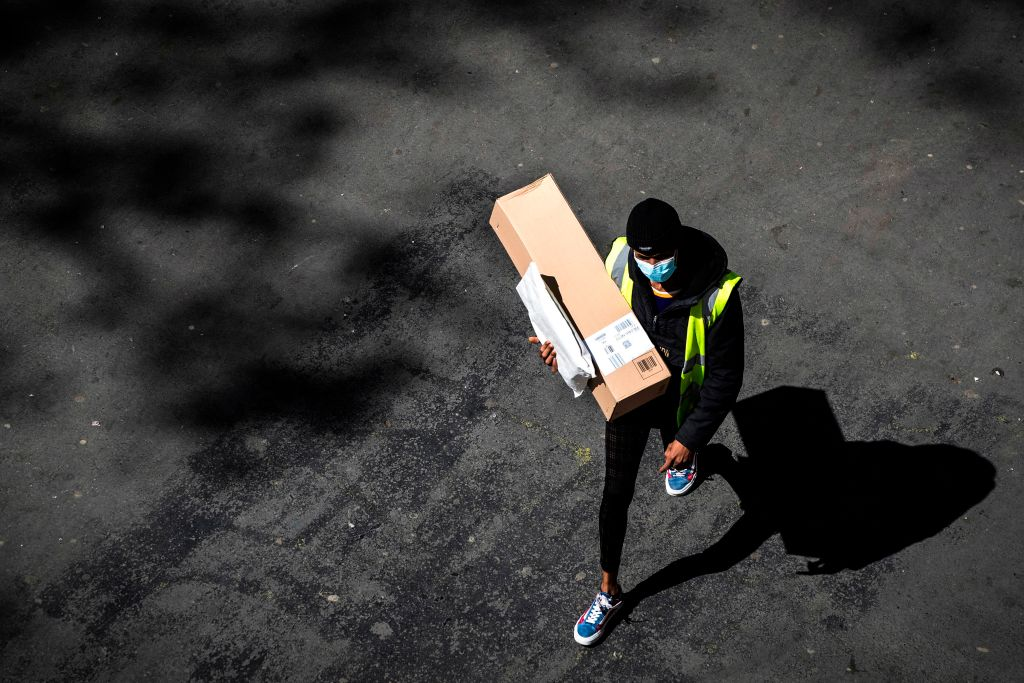 A delivery man wearing a protective mask carries an Amazon box and a letter in a street of Paris on April 15, 2020 on the 30th day of a lockdown in France aimed at curbing the spread of the COVID-19 infection caused by the novel coronavirus.
