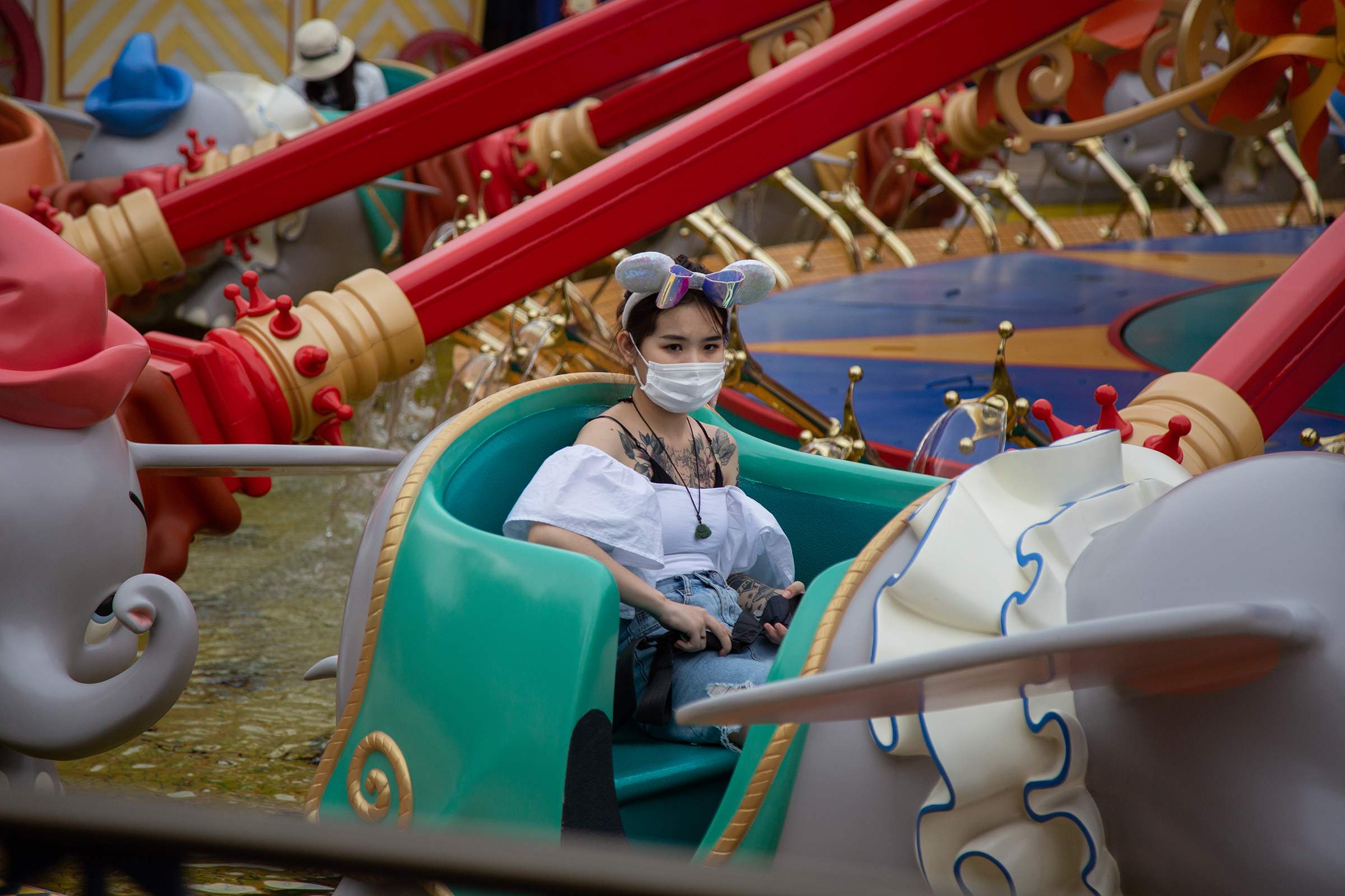 A visitor sits on the Dumbo the Flying Elephant attraction at Shanghai Disneyland on May 11, the day it reopened.