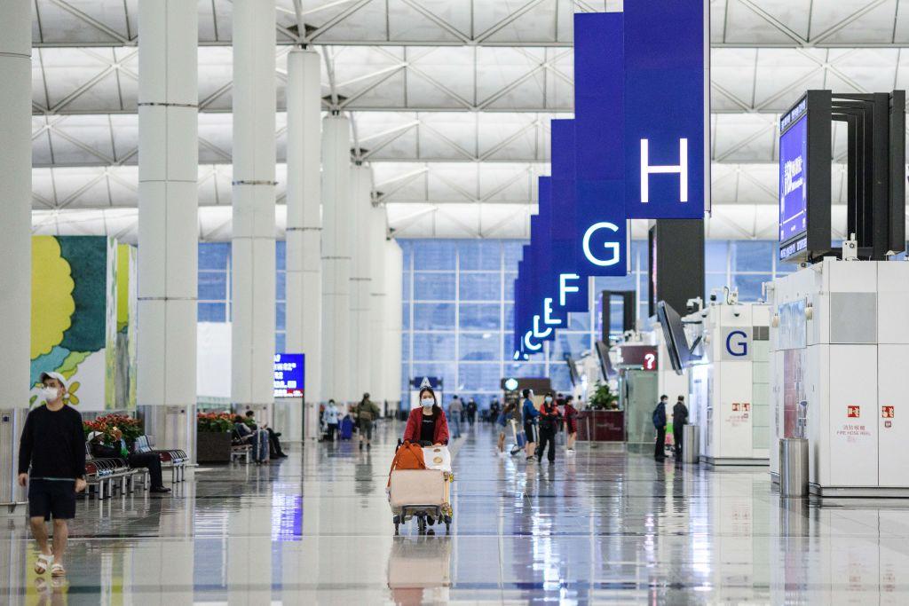 Travelers walk near the check-in counters at Hong Kong International Airport on Mar. 24, 2020.