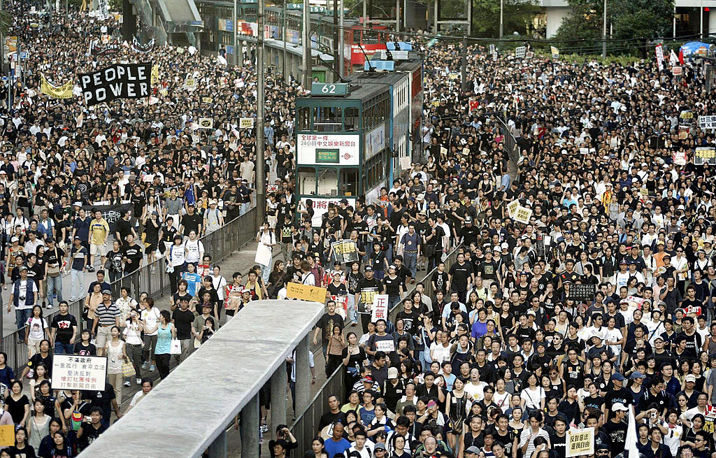 Trams sit stranded as thousands of people block the streets in a huge protest march against a controversial anti-subversion law known as Article 23 in Hong Kong on July 1, 2003.