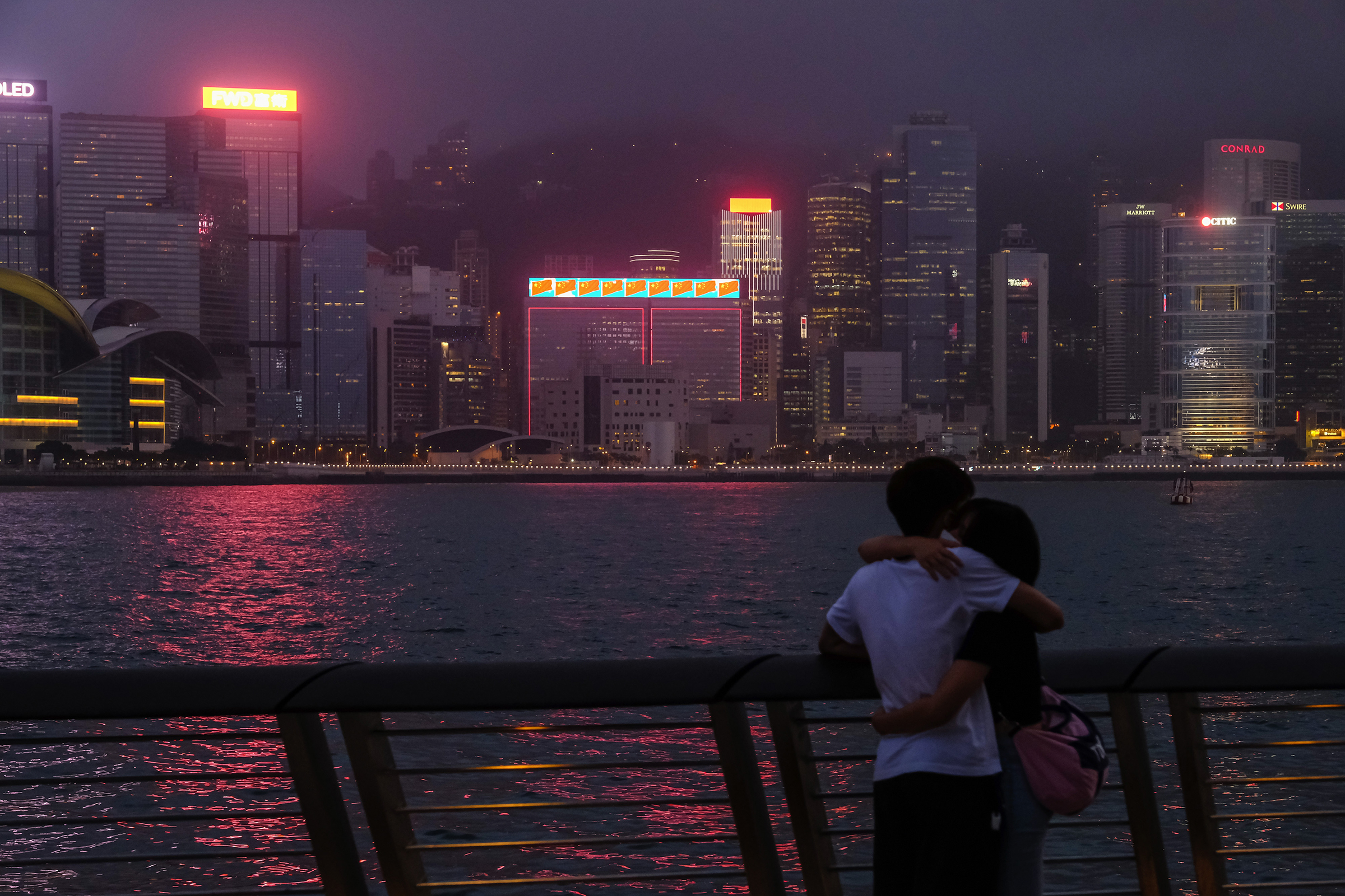 A couple across from illuminated skyscrapers on Victoria Harbor in Hong Kong on May 28, 2020.
