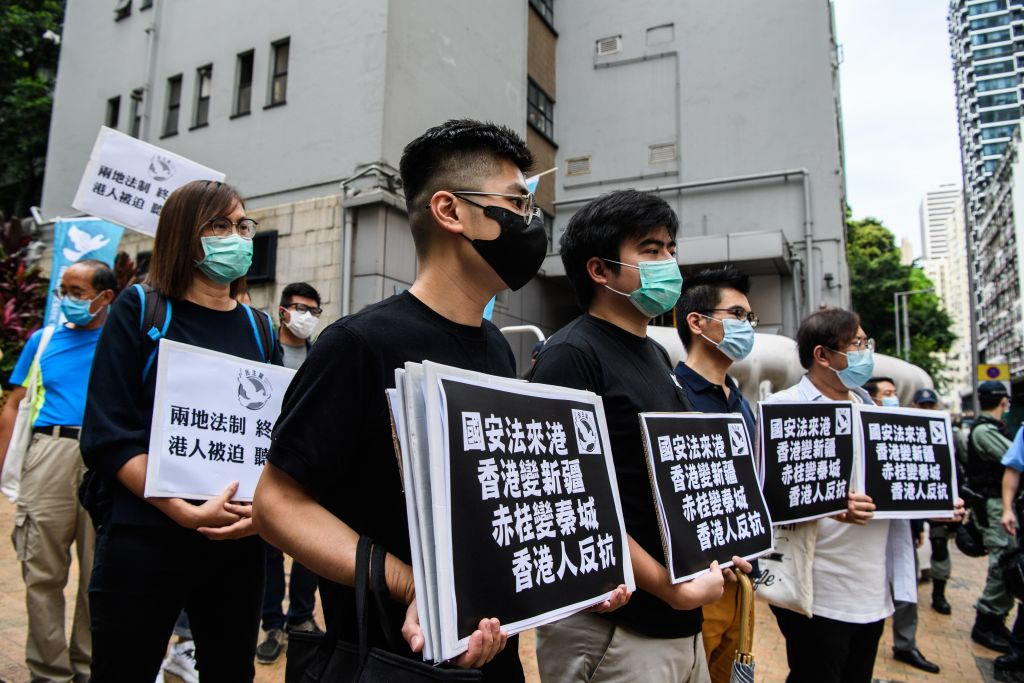 Pro-democracy protesters hold placards that translate as  National Security Law comes to Hong Kong, Hong Kong becomes Xinjiang, Stanley Prison becomes Qincheng Prison, Hong Kongers Revolt  as they march from outside the Western Police Station to the Chinese Liaison Office in Hong Kong on May 22, 2020.