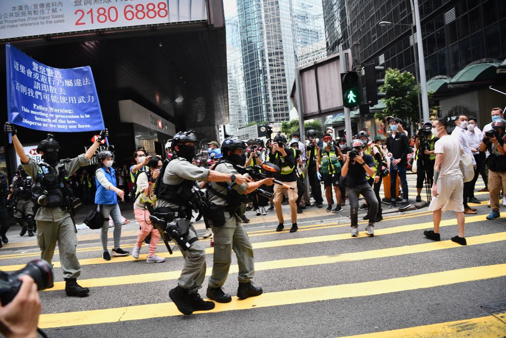 Hong Kong riot police issue a warning as they plan to clear away people gathered in the Central district of downtown Hong Kong on May 27, 2020, as the city's legislature debates over a law that bans insulting China's national anthem.