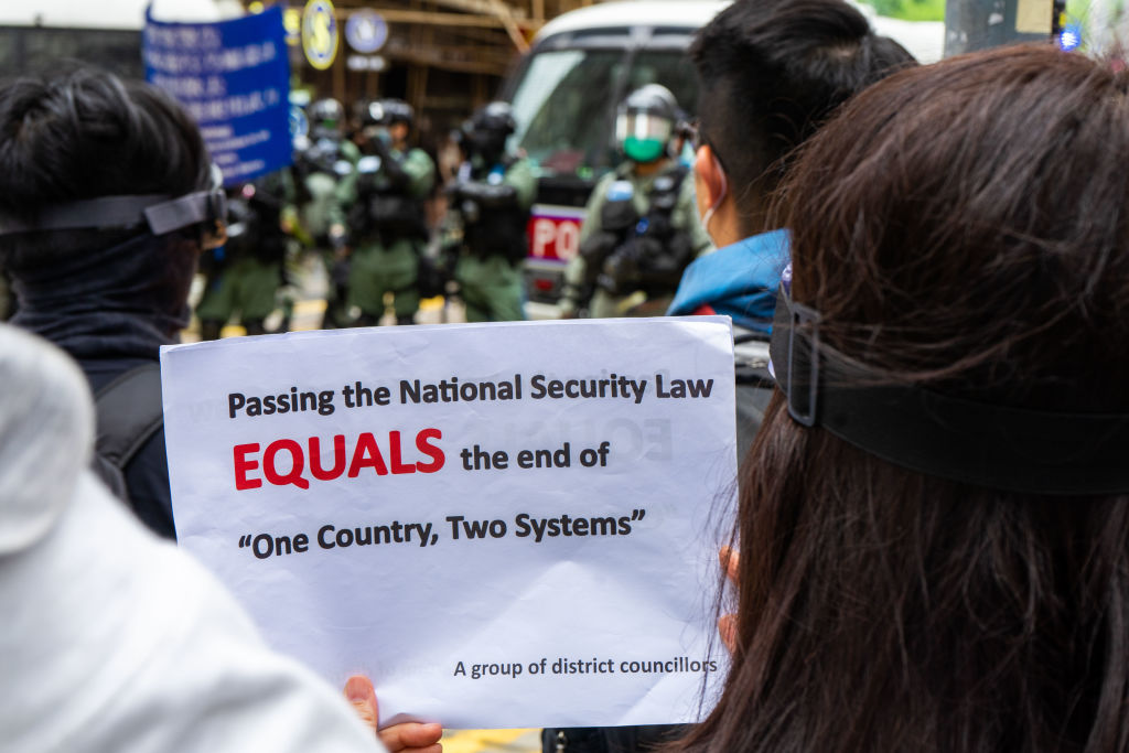 A female protester holds a placard during the anti national security bill demonstration,                       Thousands of protesters attempted to march in opposition to the national security bill drafted by the National People's Congress. Police used tear gas against the demonstrators and arrested over 100 protesters for illegal assembly.