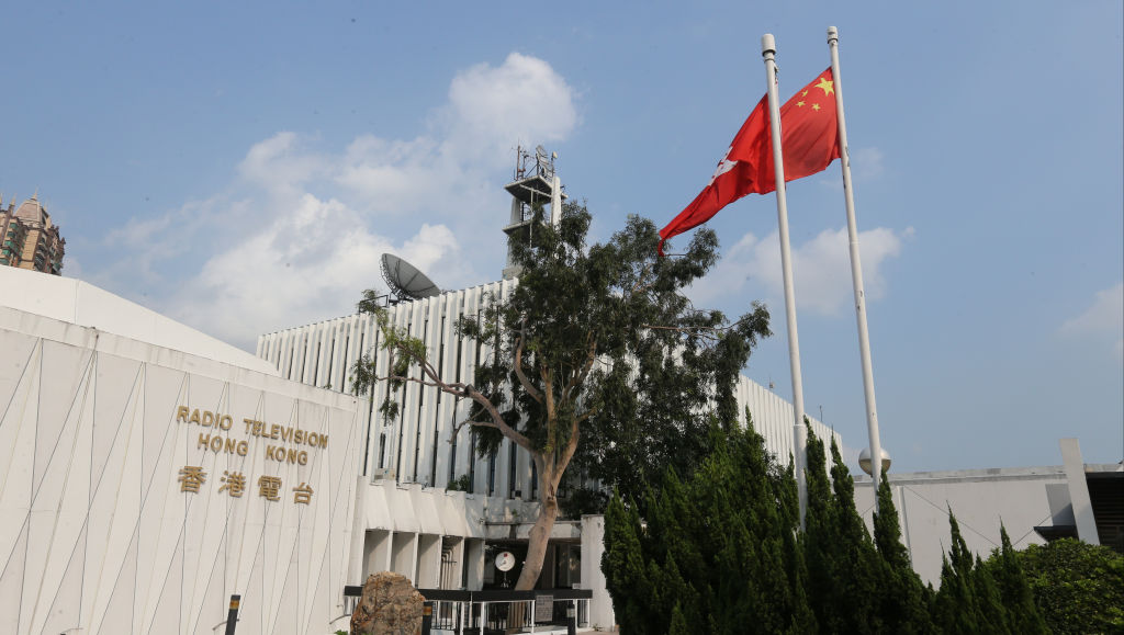 A Chinese national flag and Hong Kong flag fly in front of the Radio Television Hong Kong's offices on Aug. 6, 2015.