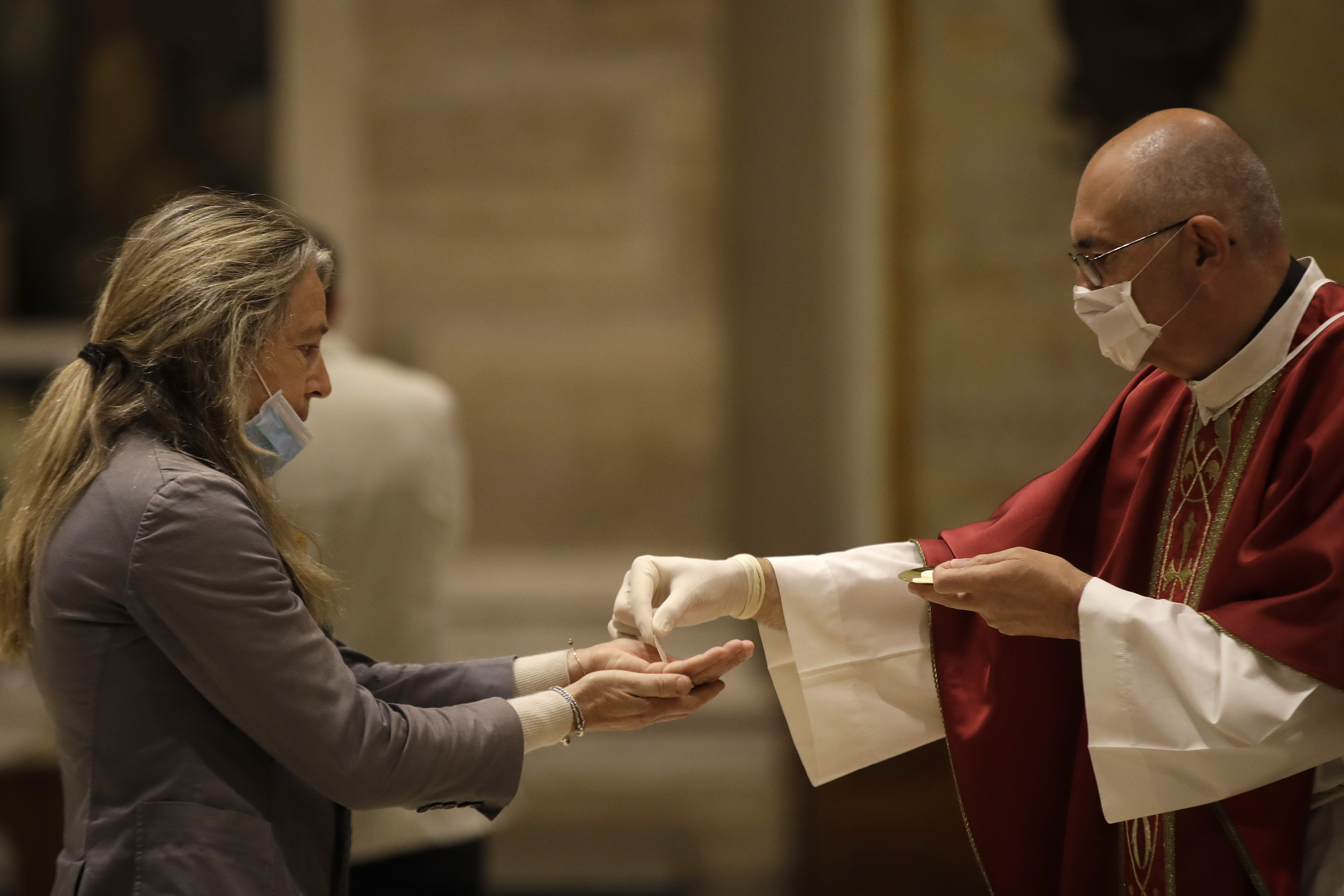 Father Jose Maria Galvan, wearing gloves to prevent the spread of COVID-19, places the host in the hands of a parishioner during the morning mass at St. Eugenio Church, in Rome, May 18, 2020.