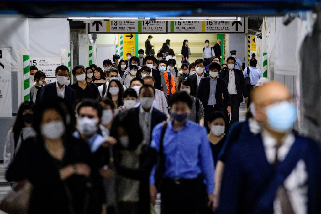 People wearing face masks, amid concerns of the COVID-19 coronavirus, walk through Shinjuku train station in Tokyo on May 25, 2020.
