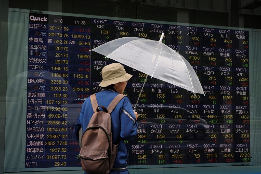 A man looks at an electronic stock quotation board of the Tokyo Stock Exchange in Tokyo on May 18, 2020.
