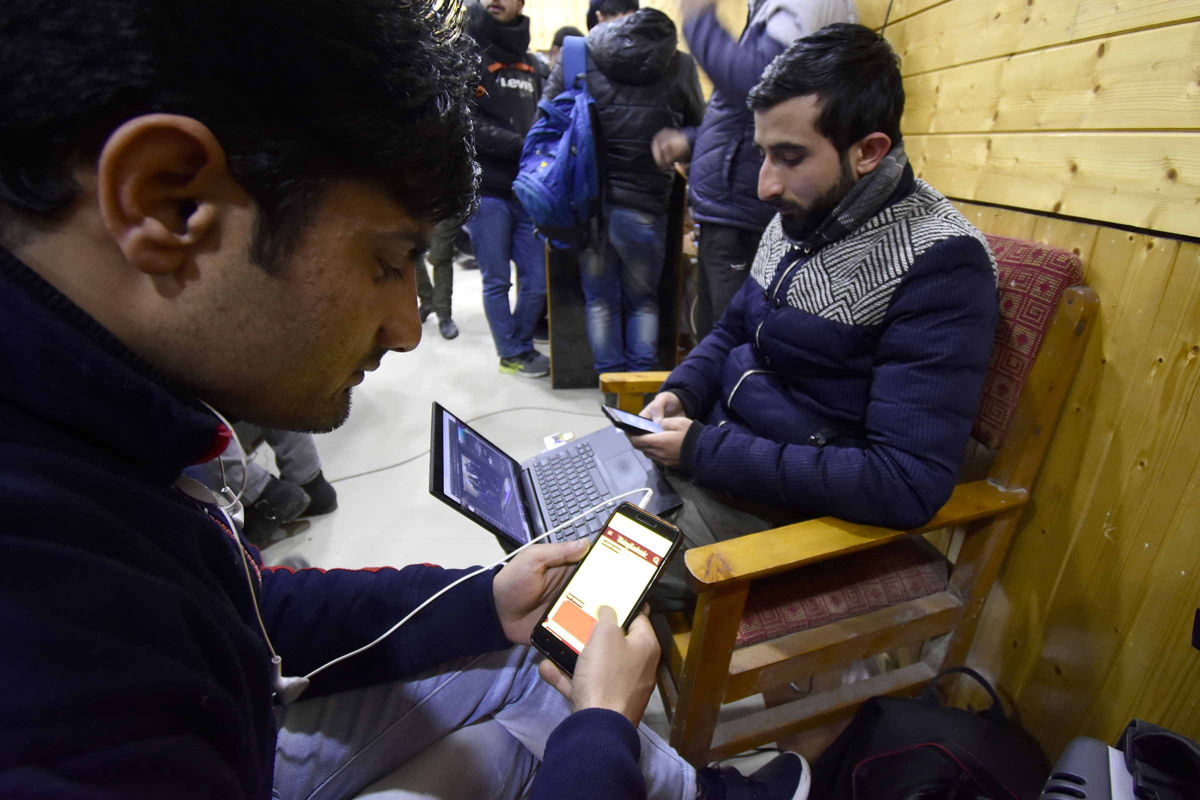Kashmiri people look at their mobile phones after authorities restored low speed mobile internet services in the Kashmir Valley on Jan. 25, 2020.