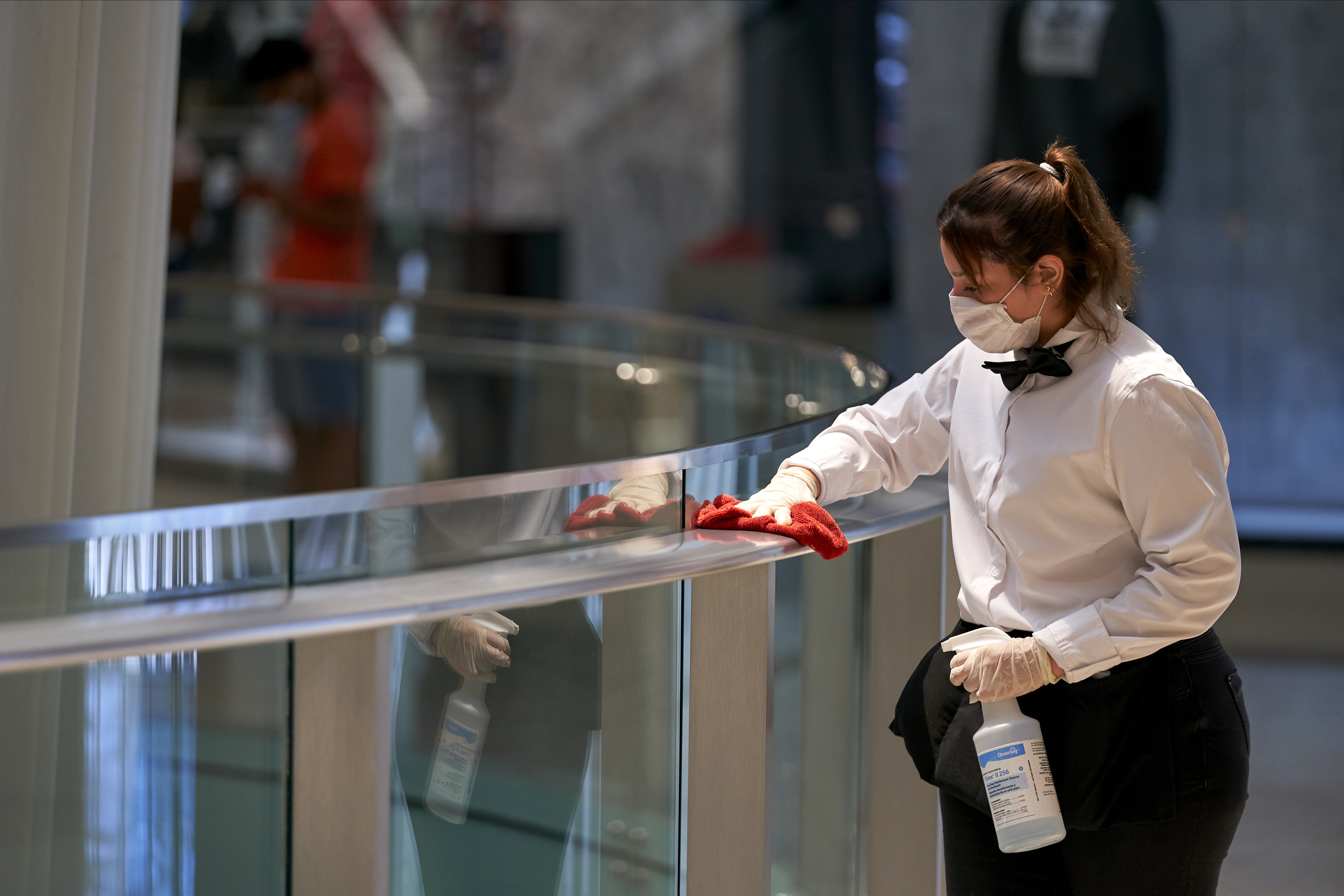 A worker disinfects hand rails at the Galleria Dallas mall in Dallas, Texas on May 4, 2020.