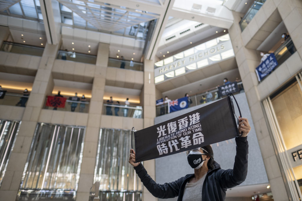 A demonstrator holds a banner reading  Liberate Hong Kong, Revolution of our Time  during a protest in Hong Kong on April 29, 2020.
