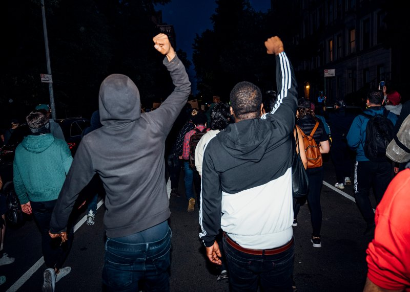 Two men walk with their fists up during a peaceful demonstration on the west side of Manhattan on May 31.