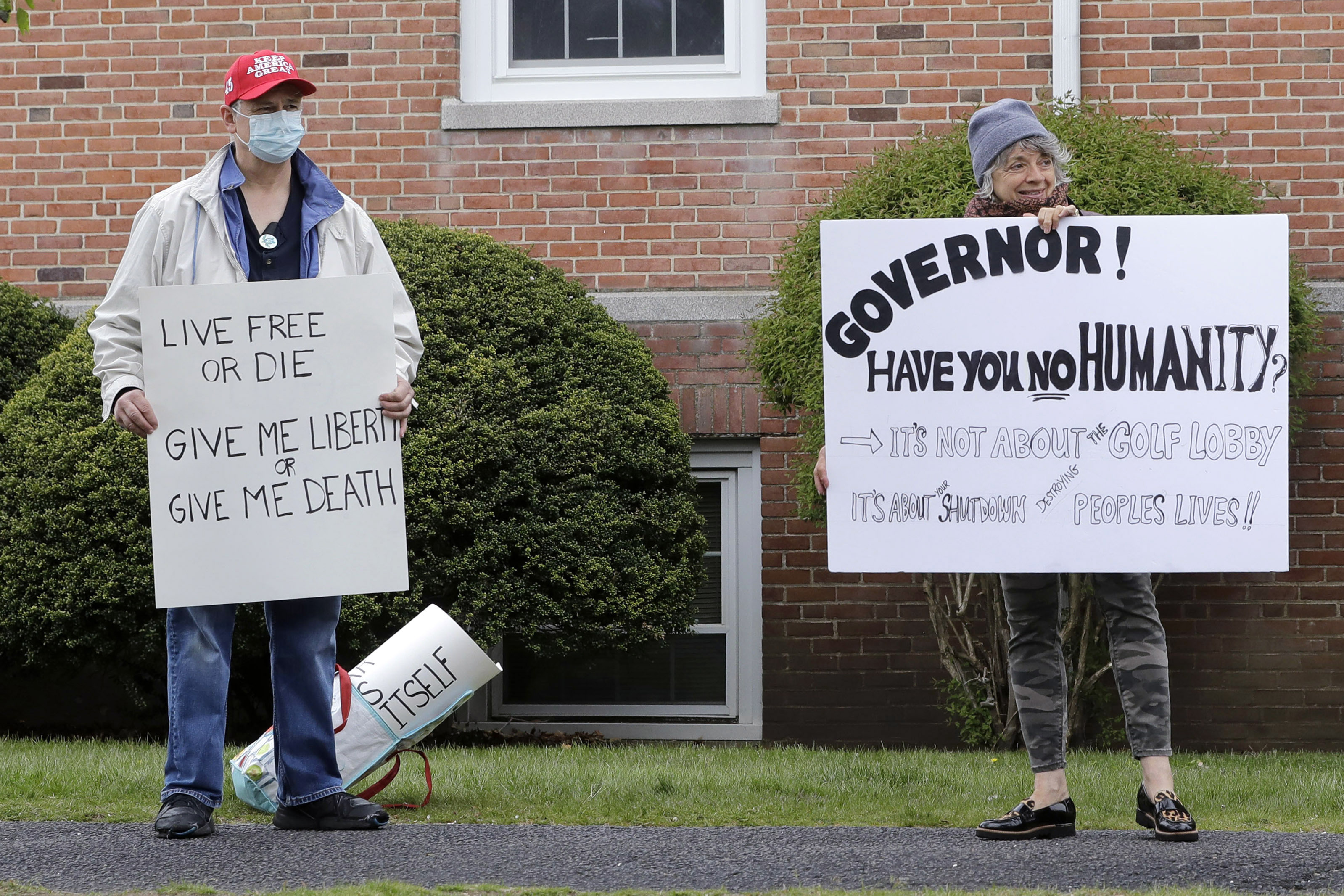 Protesters display placards while demonstrating against the shutdown caused by the COVID-19 virus outbreak, near the home of Massachusetts Gov. Charlie Baker, in Swampscott, Mass., on May 11, 2020.