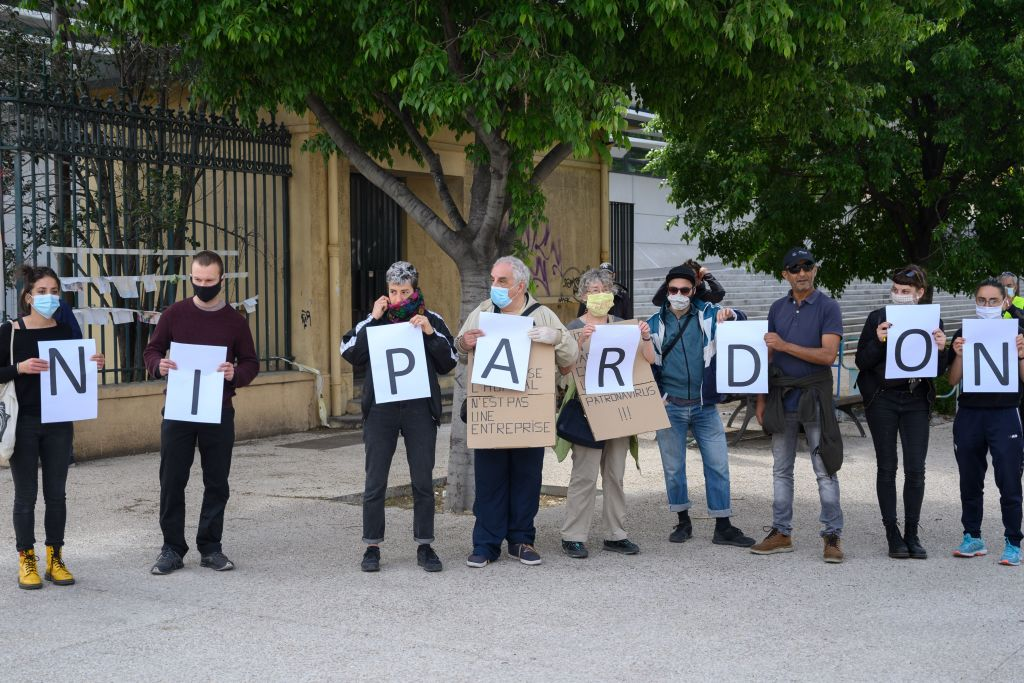 Demonstrators wearing protective masks hold placards reading:  No excuses  during the yellow vest protest to mark international May Day celebrations in front of the Timone hospital in Marseille, southern France, on May 01, 2020, during the strict lockdown across France aimed at curbing the spread of the COVID-19 pandemic, caused by the novel coronavirus on the 46th day of lockdown.