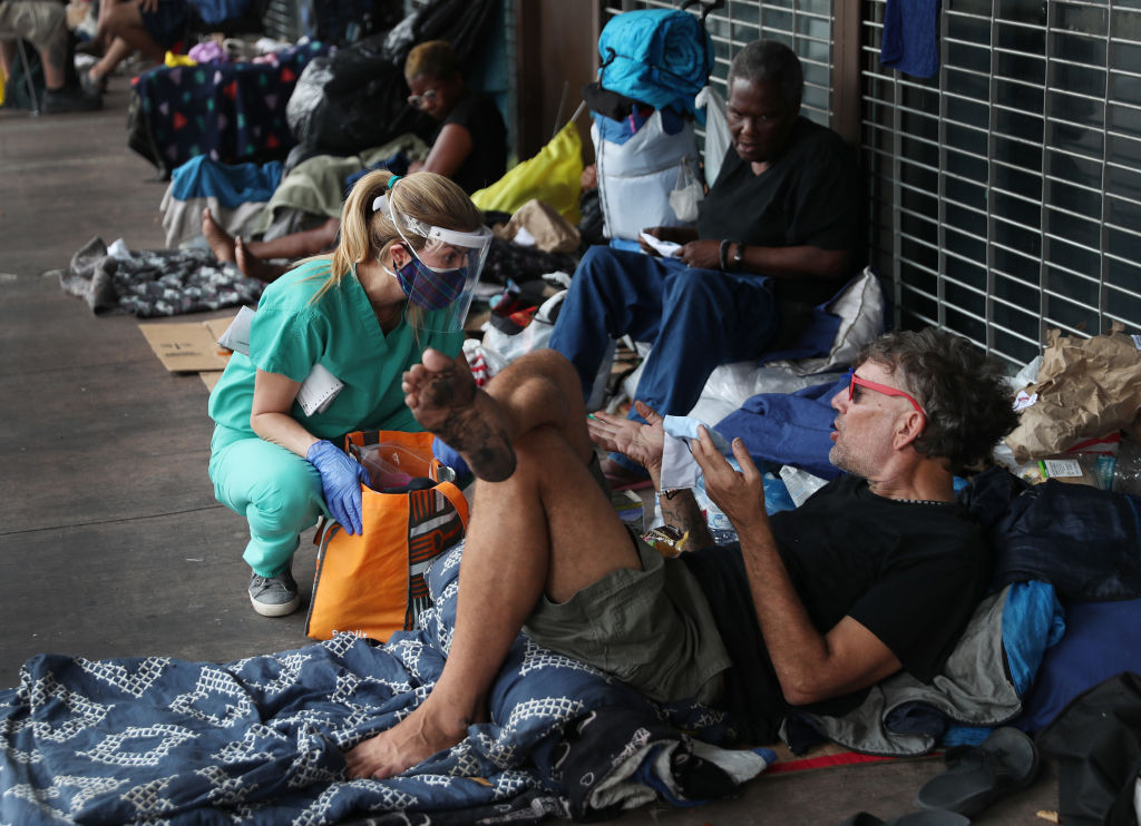 Dr. Natalia Echeverri asks Star Lee Black if he needs a COVID-19 test or anything else as she checks on the homeless on April 17, 2020 in Miami, Florida.