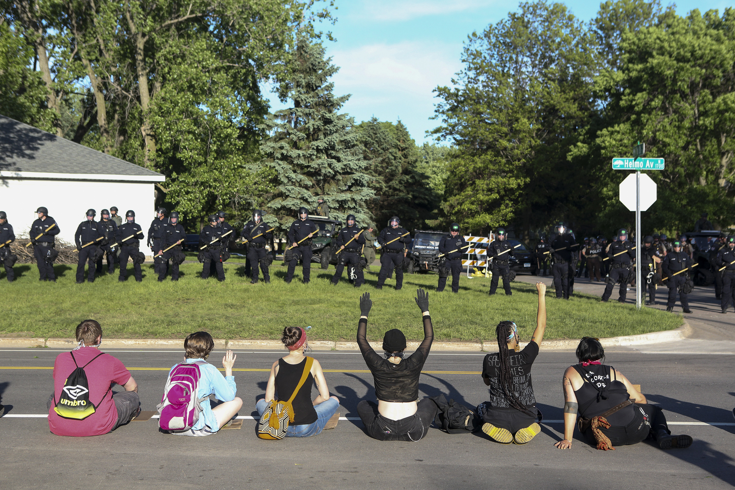 Demonstrators sit before a police line outside the home of Derek Chauvin, the since-fired Minneapolis officer who pinned down George Floyd with a knee on his neck, in the suburb of Oakdale on May 28.