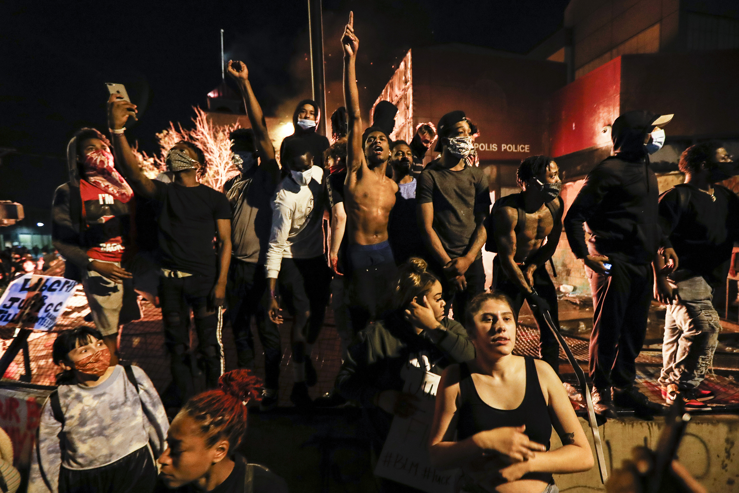 Protesters demonstrate outside of the burning precinct on May 28.