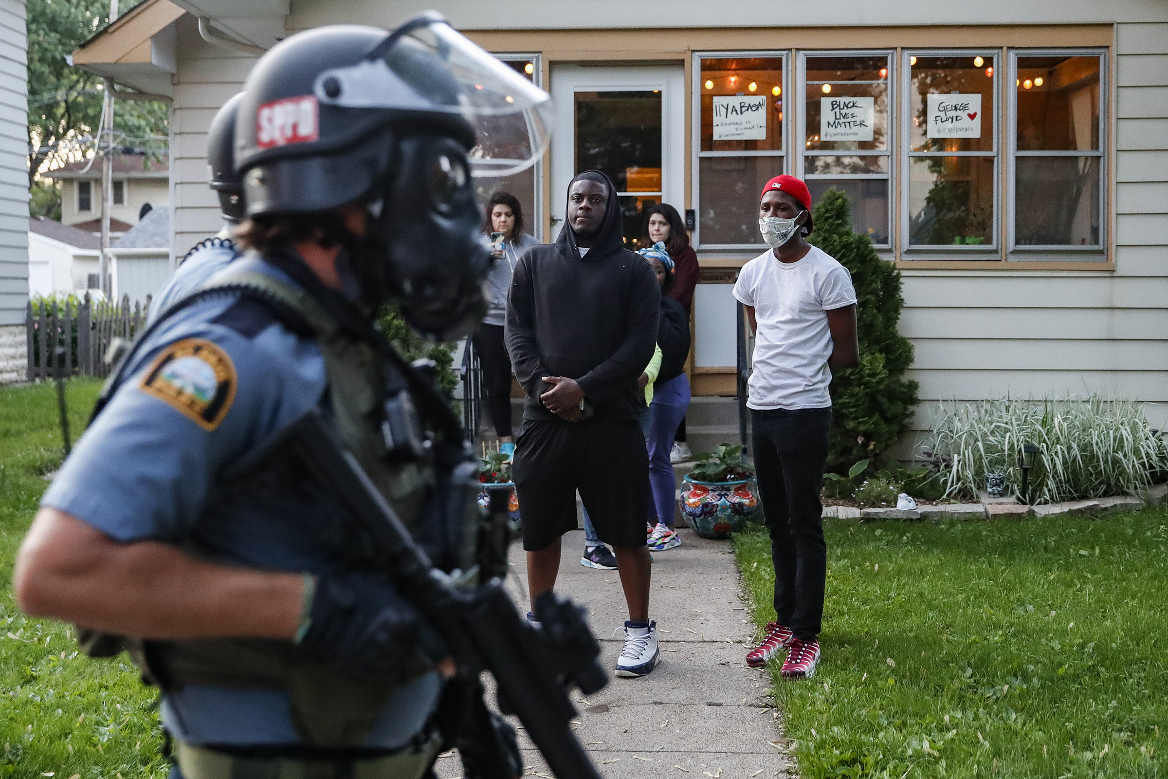 Protesters watch as police in riot gear walk down a residential street in St. Paul, Minn., on May 28.