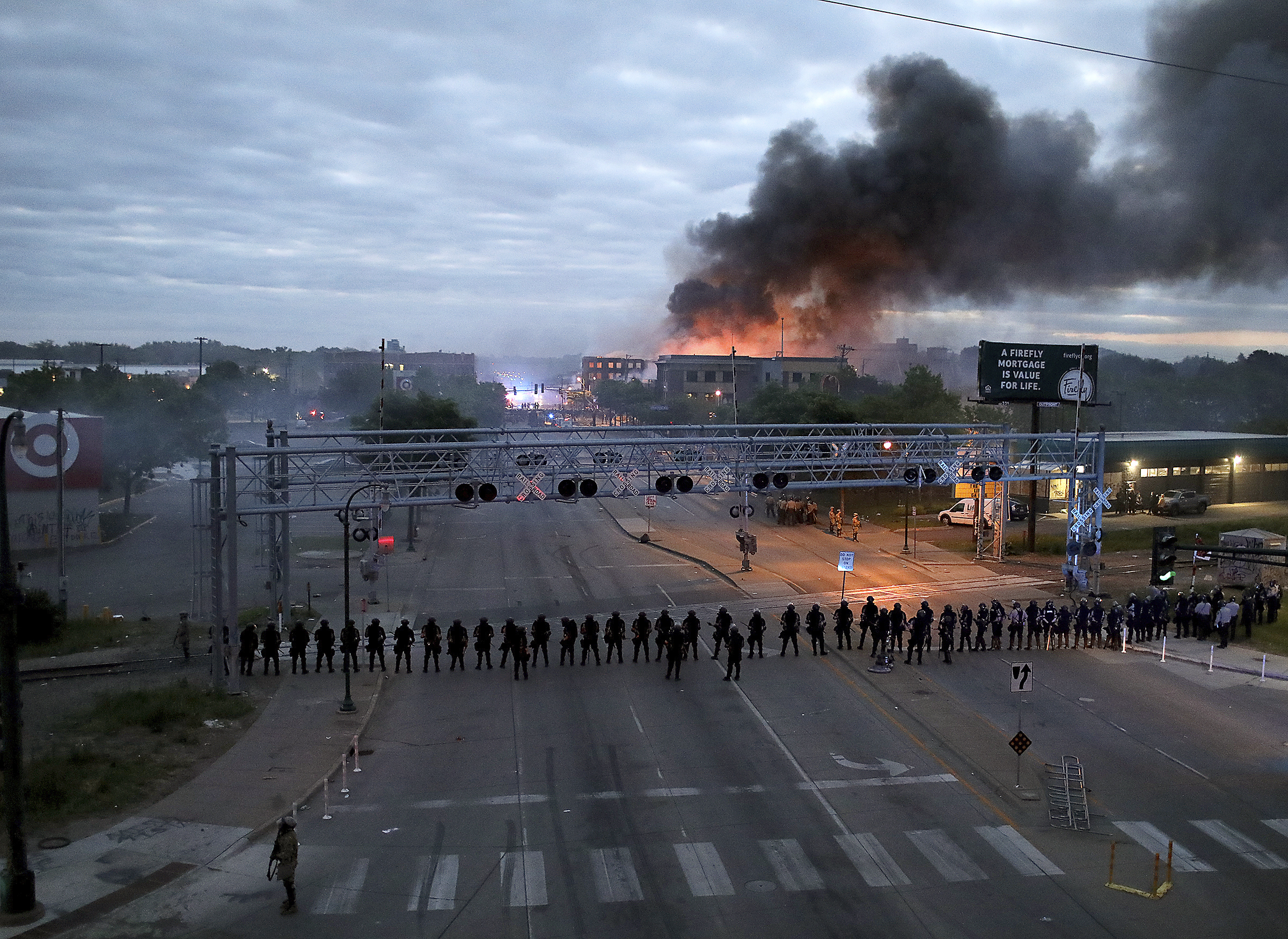 Law enforcement officers amassed along Lake Street near Hiawatha Avenue as fires burned after a night of unrest and protests in Minneapolis on May 29.
