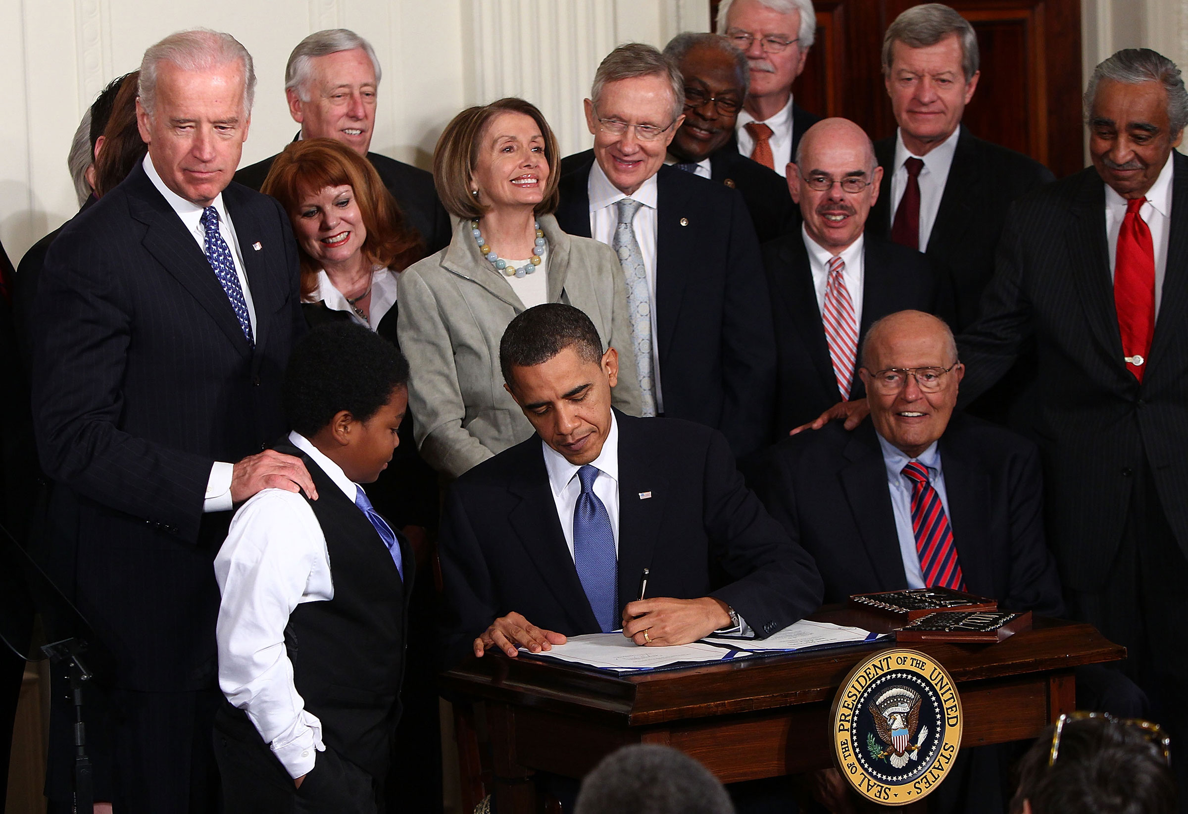 President Barack Obama signs the Affordable Health Care for America Act during a ceremony with fellow Democrats in the East Room of the White House March 23, 2010.