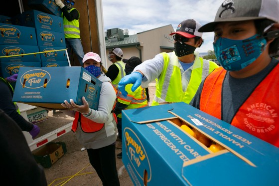 Navajo Nation President Jonathan Nez, center, and Isaiah Tsosie, right, an office specialist with the Coyote Canyon chapter, move food for distribution in Coyote Canyon, N.M., on the Navajo Nation on May 15, 2020.