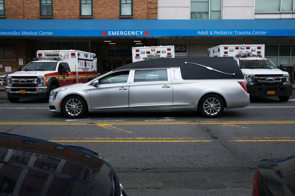 A hearse drives past medical workers outside a special coronavirus area at Maimonides Medical Center on May 11, 2020 in the Borough Park neighborhood of the Brooklyn borough of New York City.