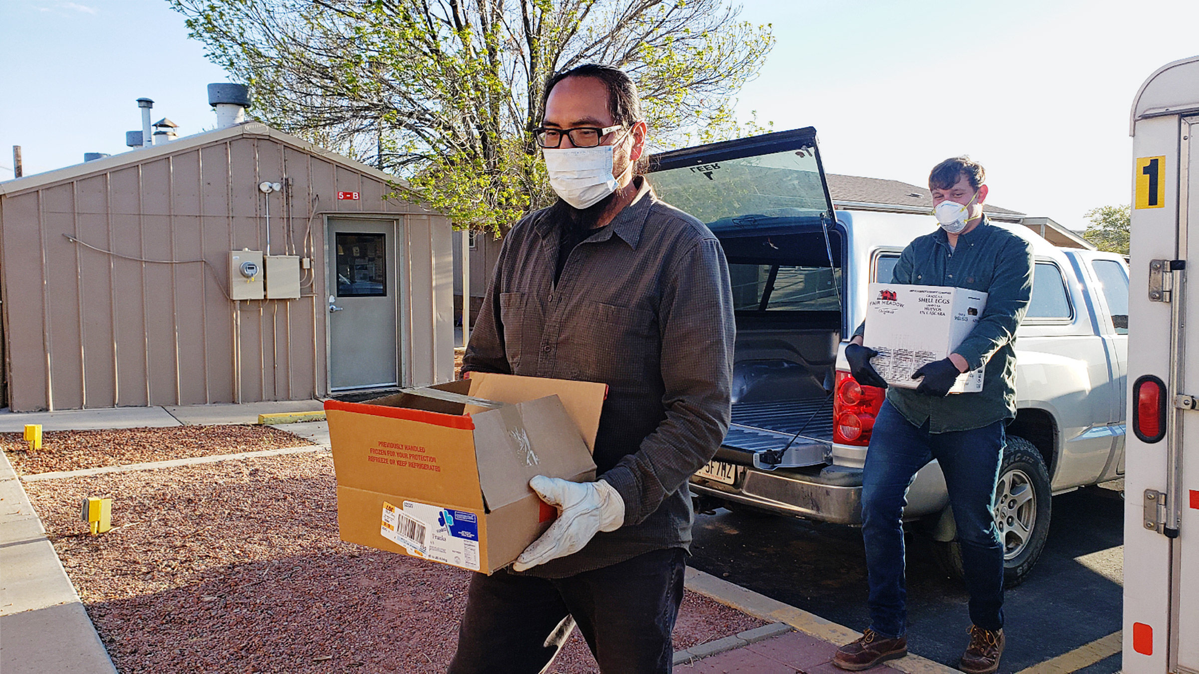Pete Sands carries boxes of food and cleaning supplies to Navajo Nation members in need.