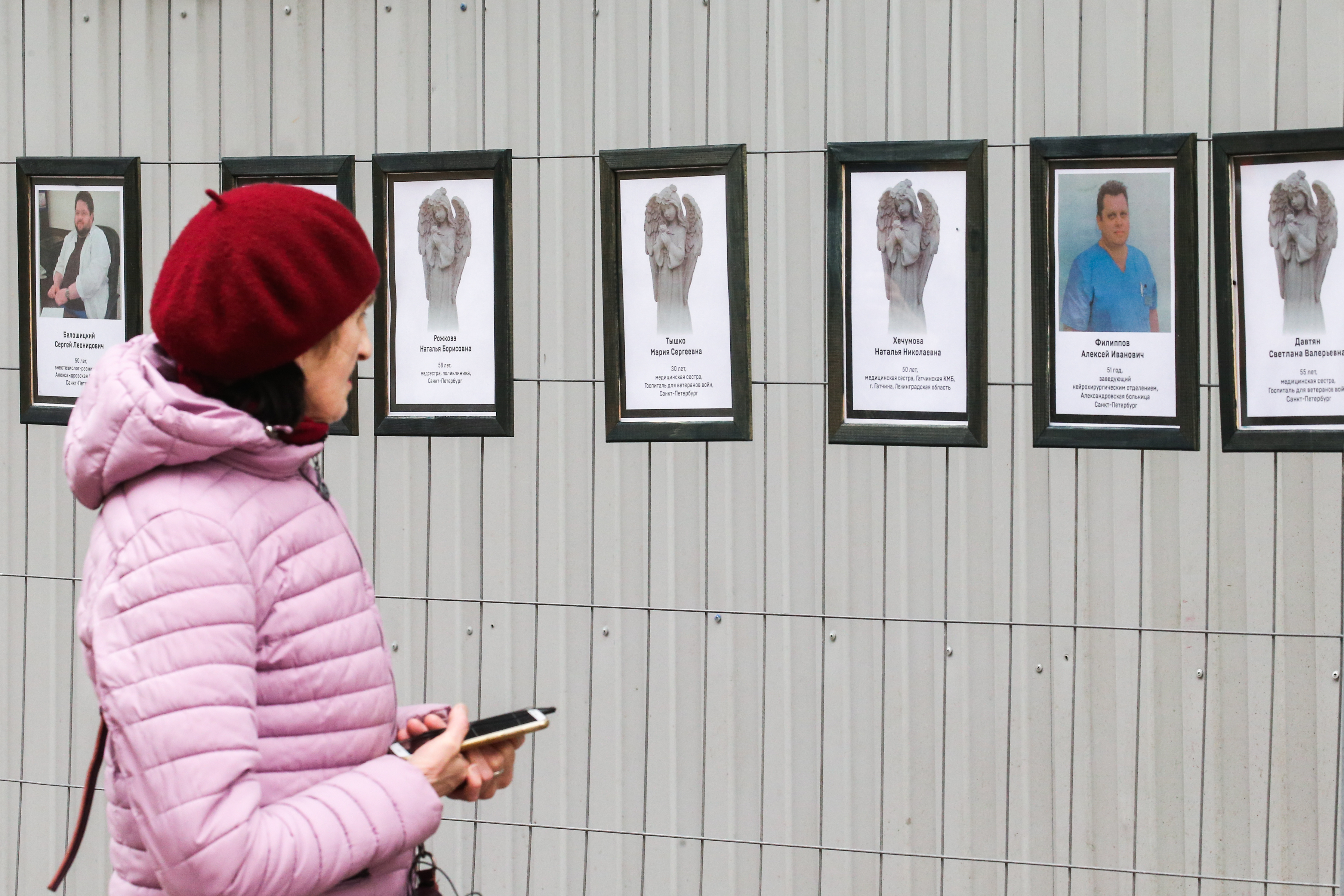 A woman walks by portraits of medical workers who died after contracting the novel coronavirus by the offices of St Petersburg's Healthcare Committee in St. Petersburg, Russia on April 28, 2020.