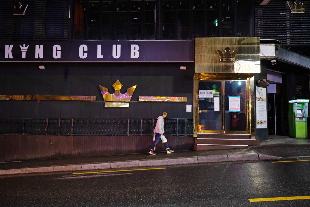A person wearing a protective face mask walks past a closed club at night in the Itaewon area of Seoul, South Korea, on Saturday, May 9, 2020.