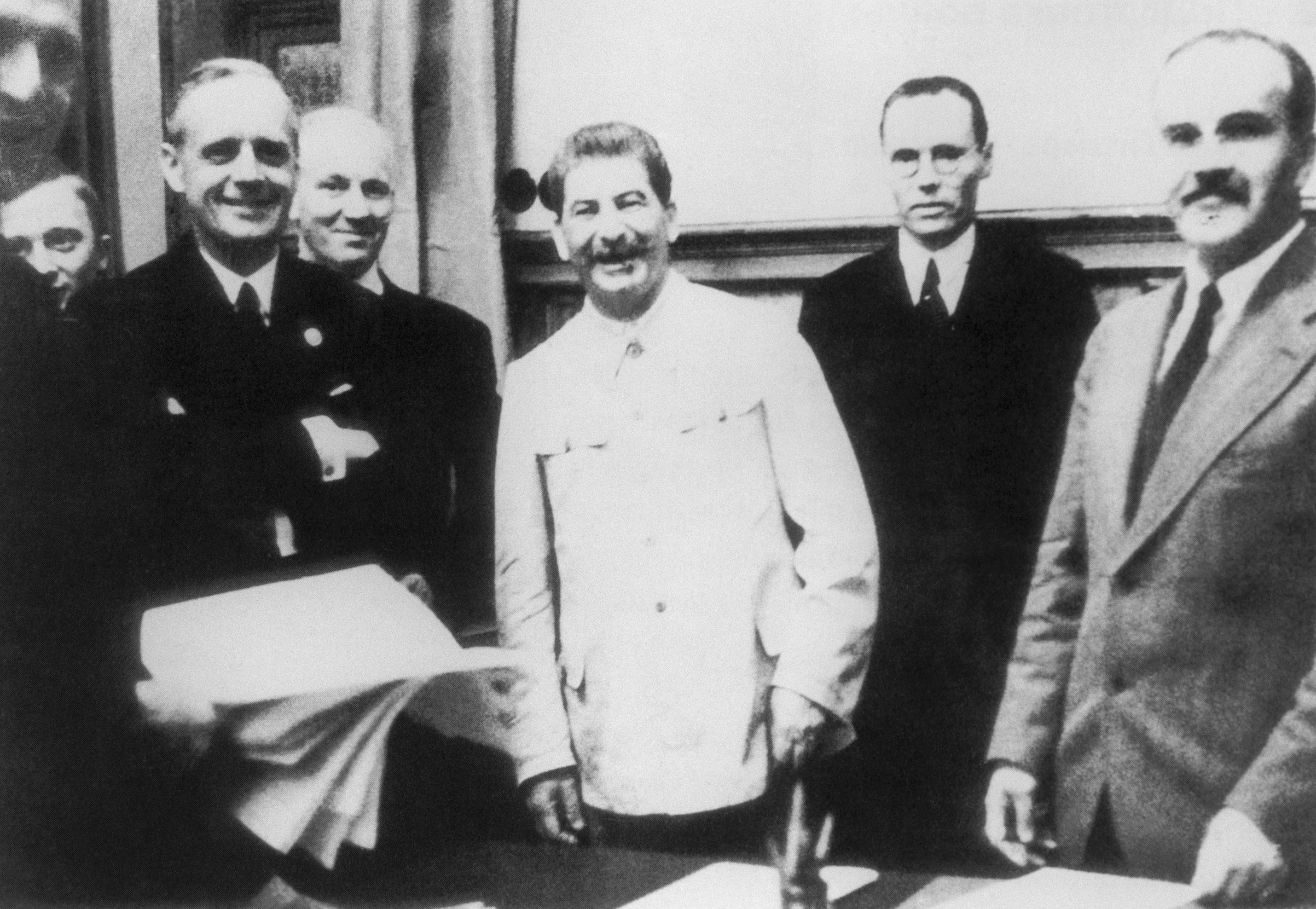The Foreign Minister of Germany, Joachim von Ribbentrop, Soviet Leader Iosif (Joseph) Stalin and Soviet foreign minister Vyacheslav Molotov (foreground L-R) pose for a photo at the singing ceremony of the German-Soviet Treaty of Nonaggression, Aug. 23, 1939, in Moscow