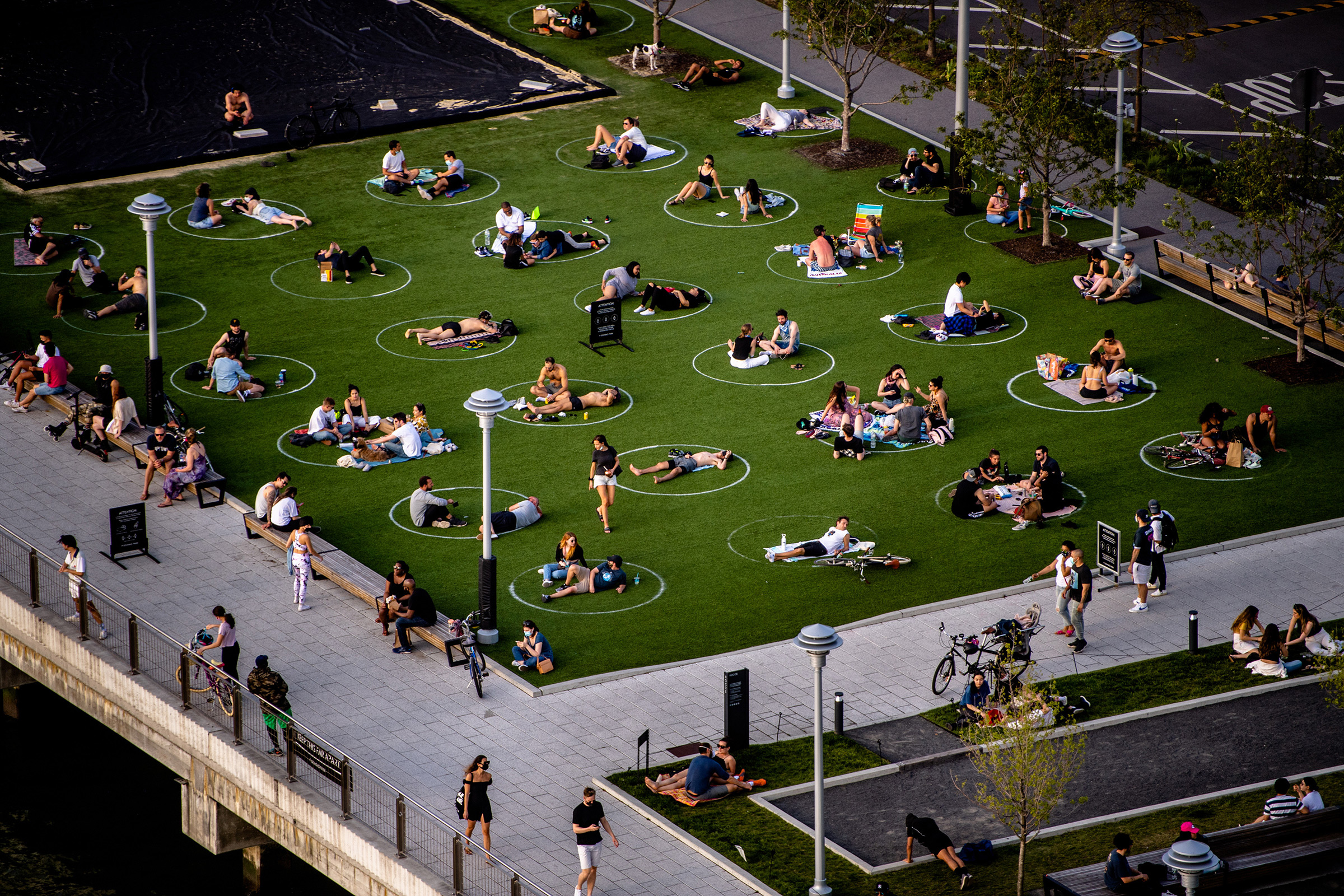 People sit in marked circles to promote social distancing in Brooklyn on May 15, as cities across America adopt new policies to reopen