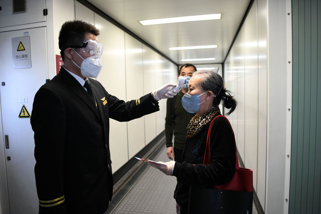 A passenger boarding a Shenzhen Airlines flight has temperature checked at the Baoan International Airport in Shenzhen, China, on April 8, 2020.
