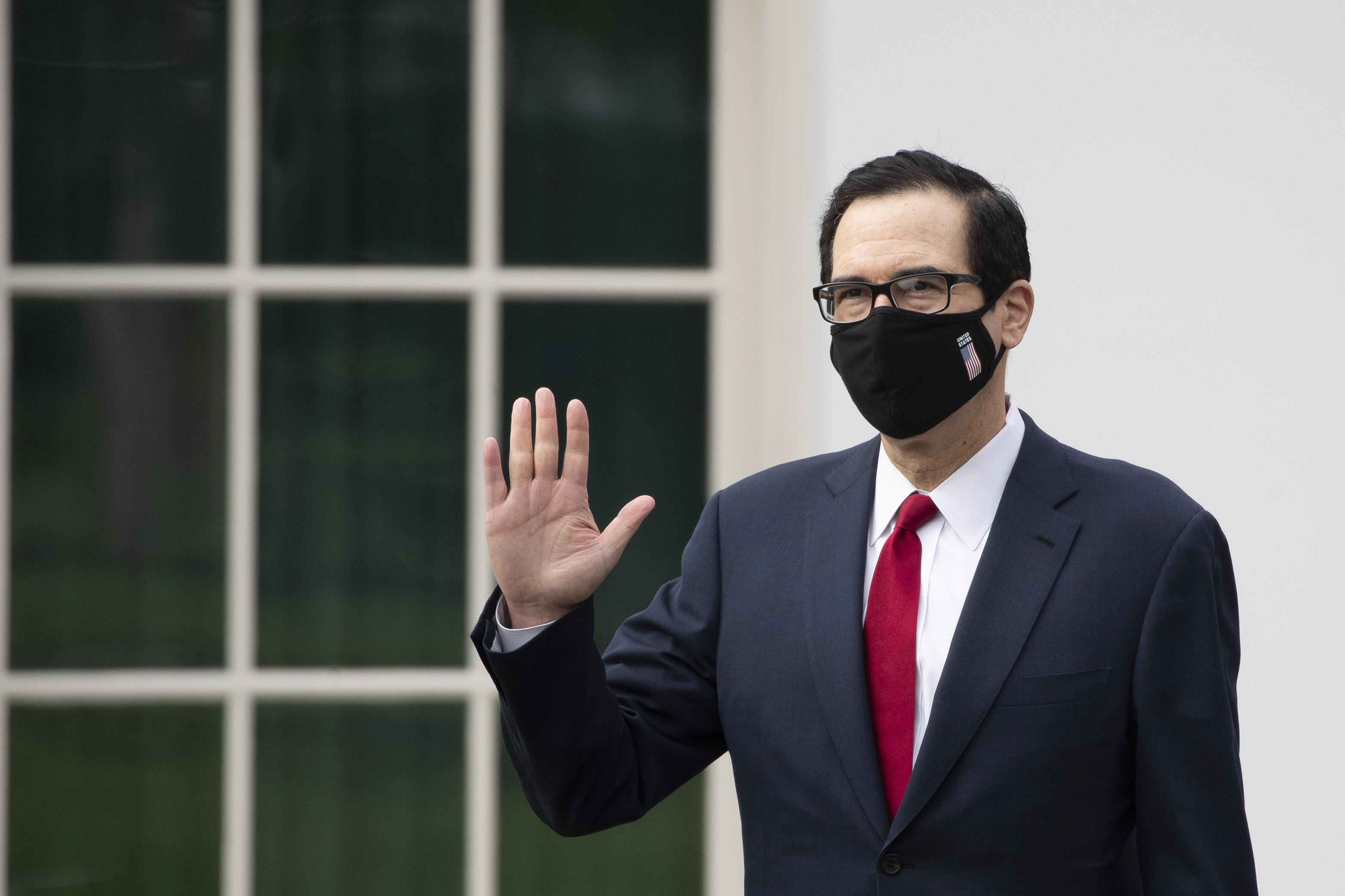 Treasury Secretary Steven Mnuchin wears a mask as he walks on the grounds of the White House, on May 14, 2020, in Washington.