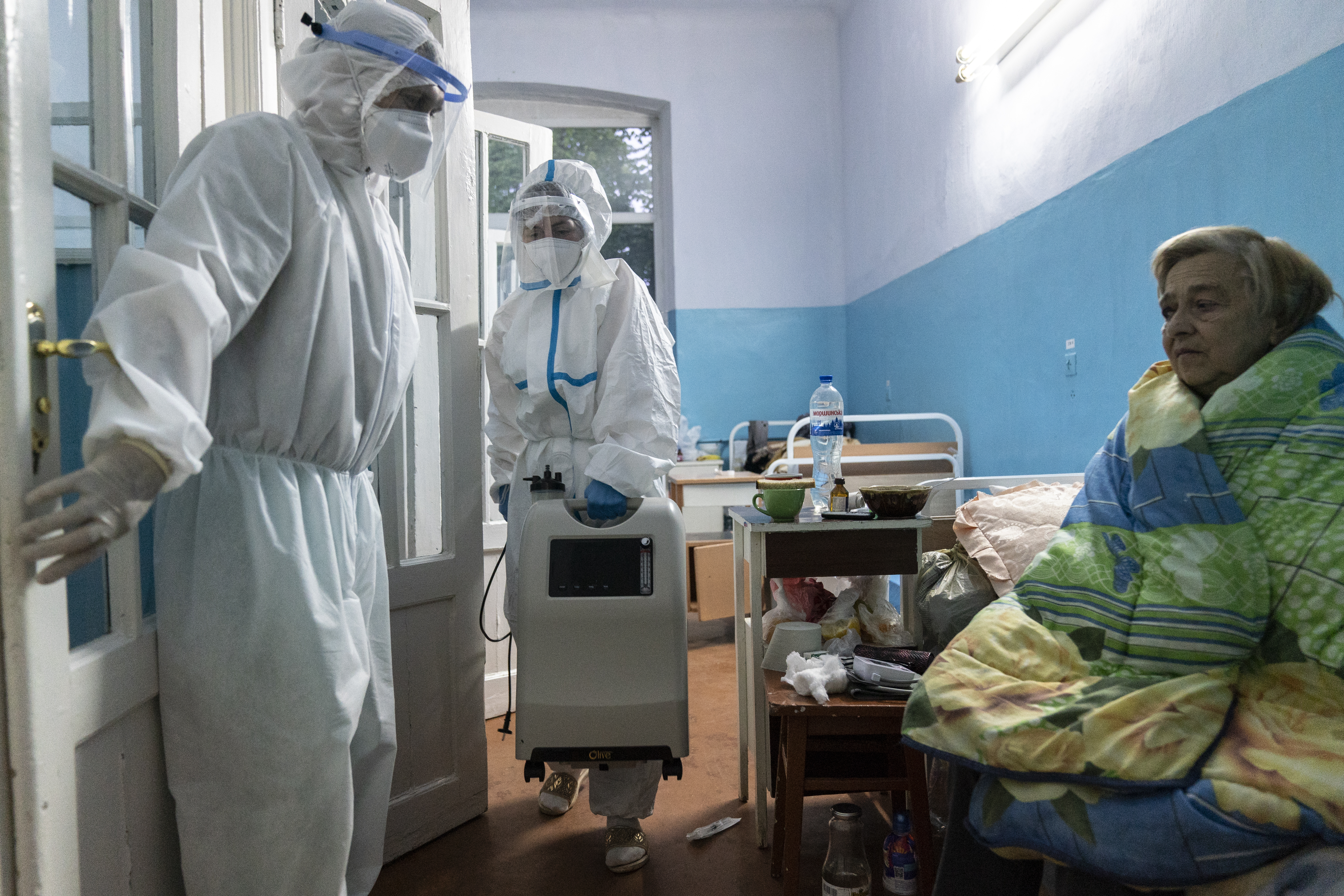 In this photo taken on May 9, 2020, a nurse, carries medical equipment to help a patient suspected of having the coronavirus infection at a the regional hospital in Chernivtsi, Ukraine.