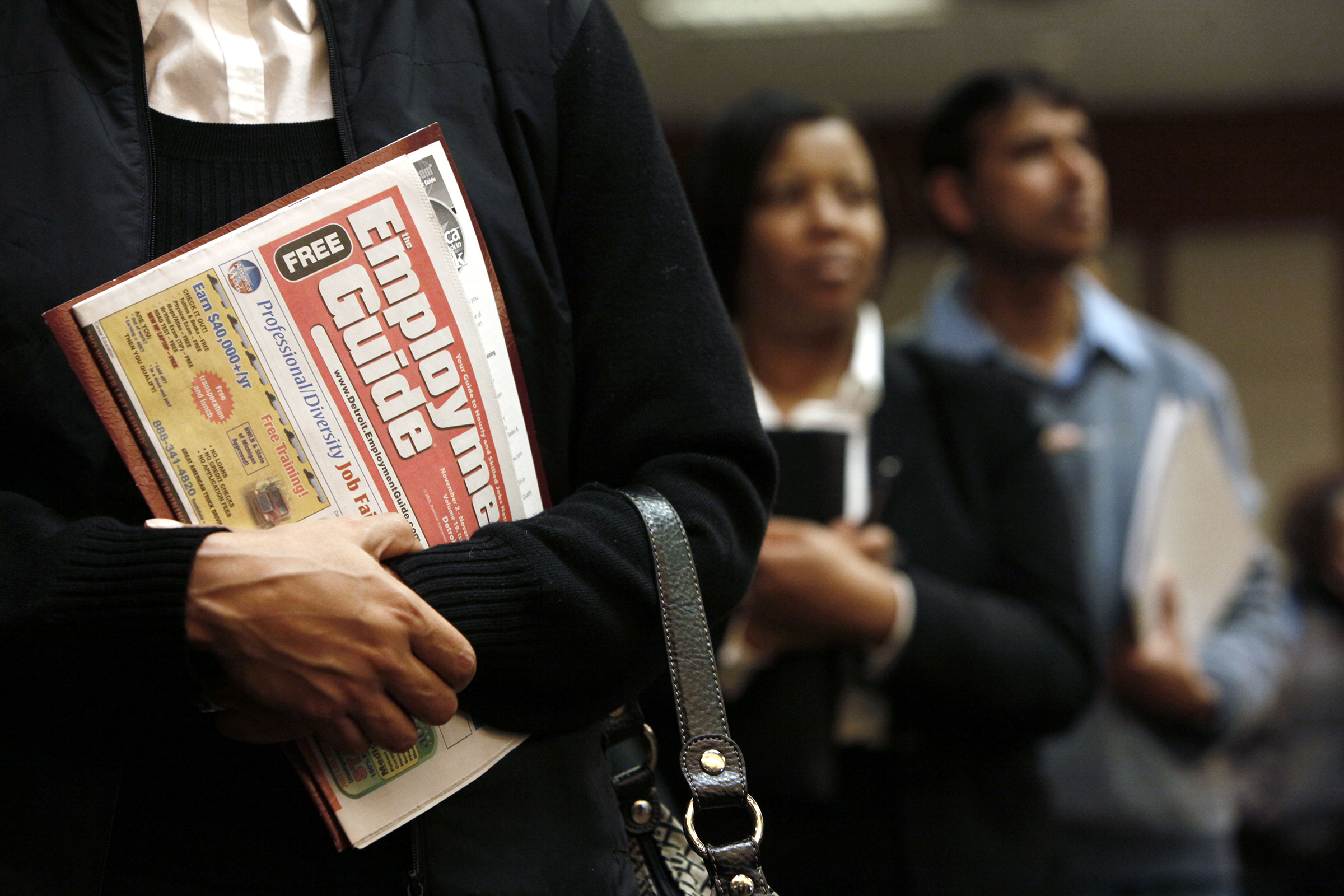 A woman holds an employment guide standing in line while attending a job fair in Livonia, Michigan, on Nov. 4, 2009.