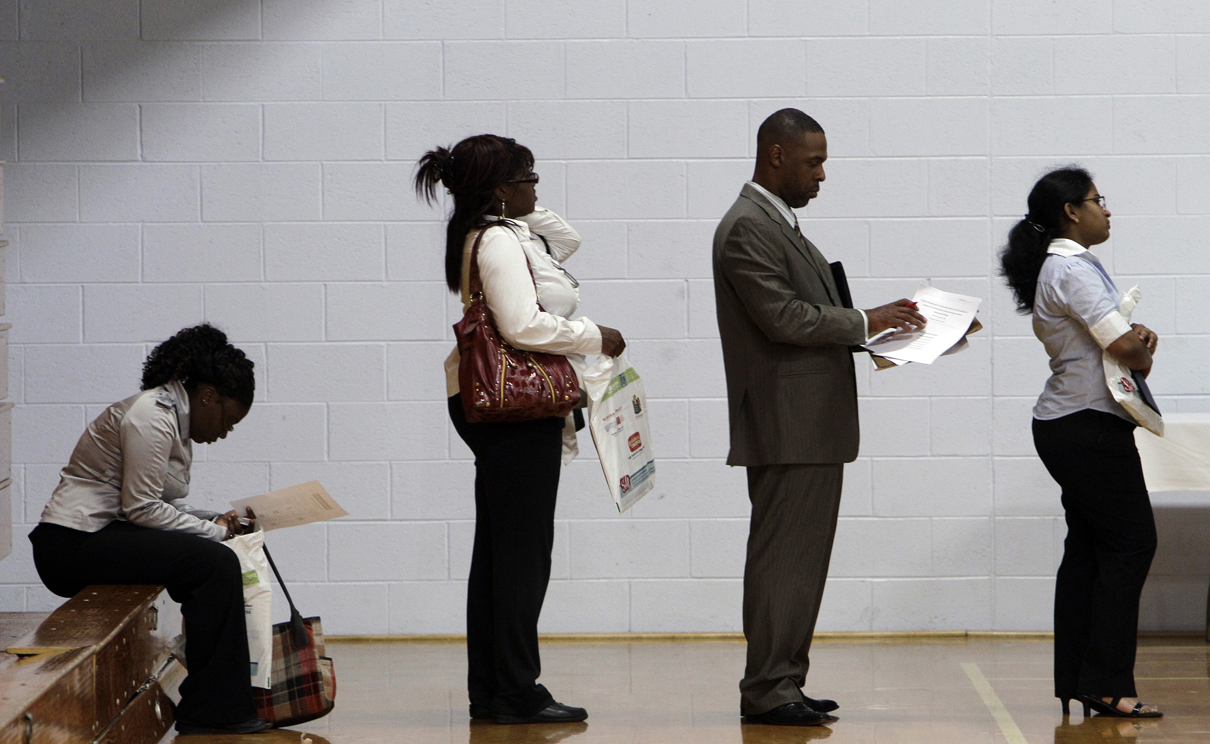 Job seekers wait in a line at a job fair in Southfield, Michigan on June 15, 2011.