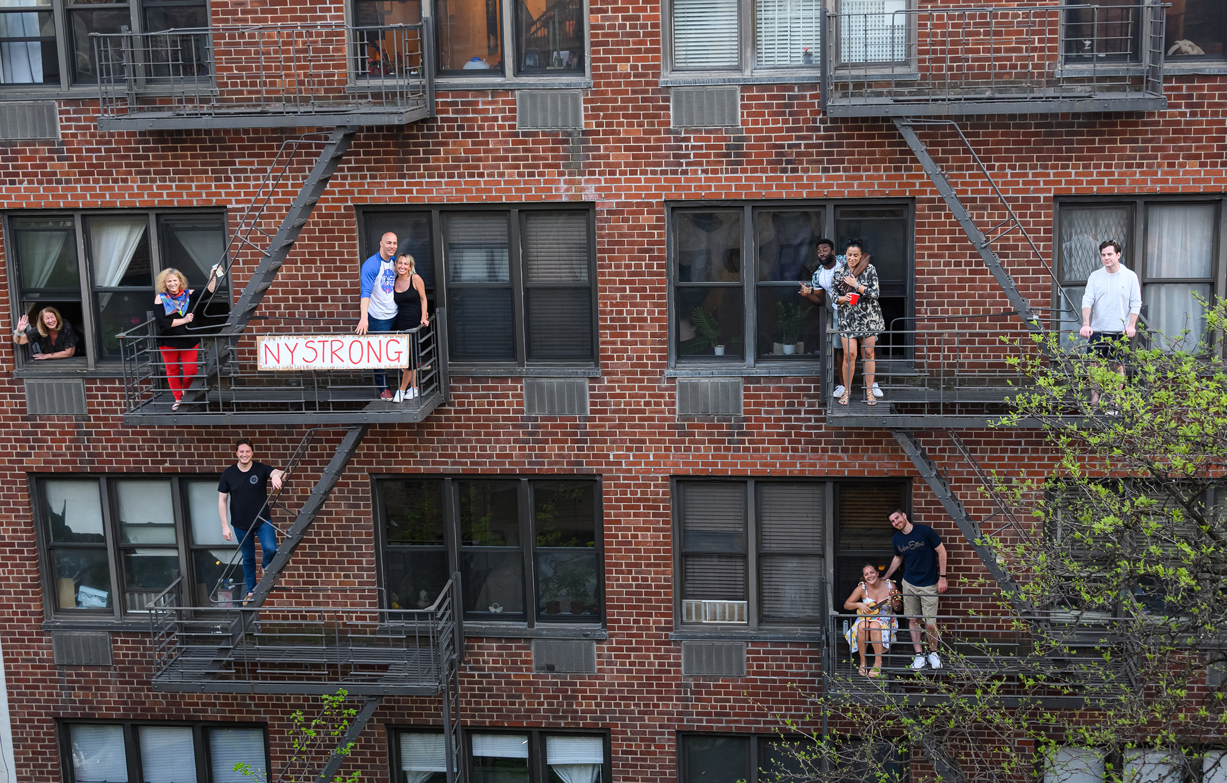 People applaud from their fire escapes to show their gratitude to medical staff and essential workers on the front lines of the coronavirus pandemic during the coronavirus pandemic in the Upper East Side on May 2nd in New York City.