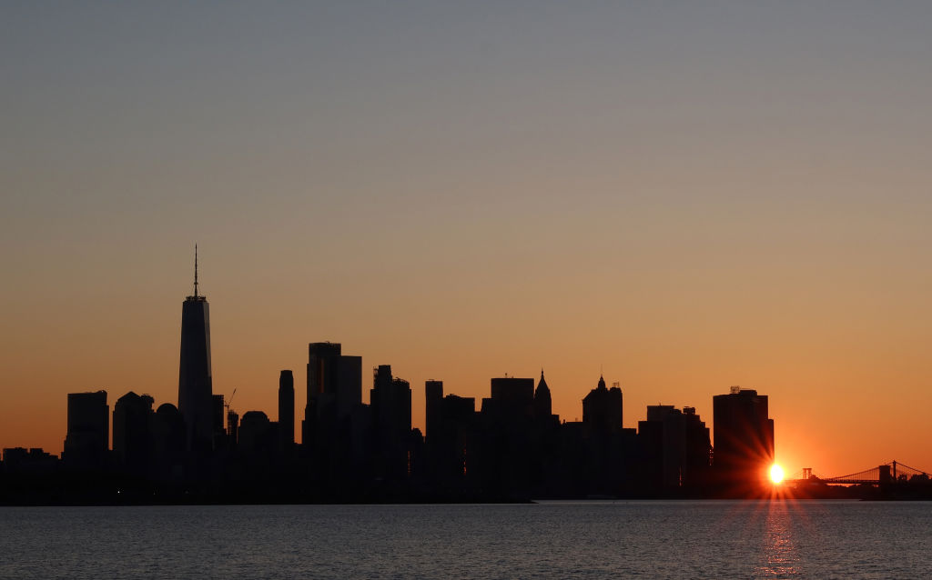 The sun rises behind the skyline of lower Manhattan, and One World Trade Center in New York City on May 2, 2020 as seen from Jersey City, New Jersey.