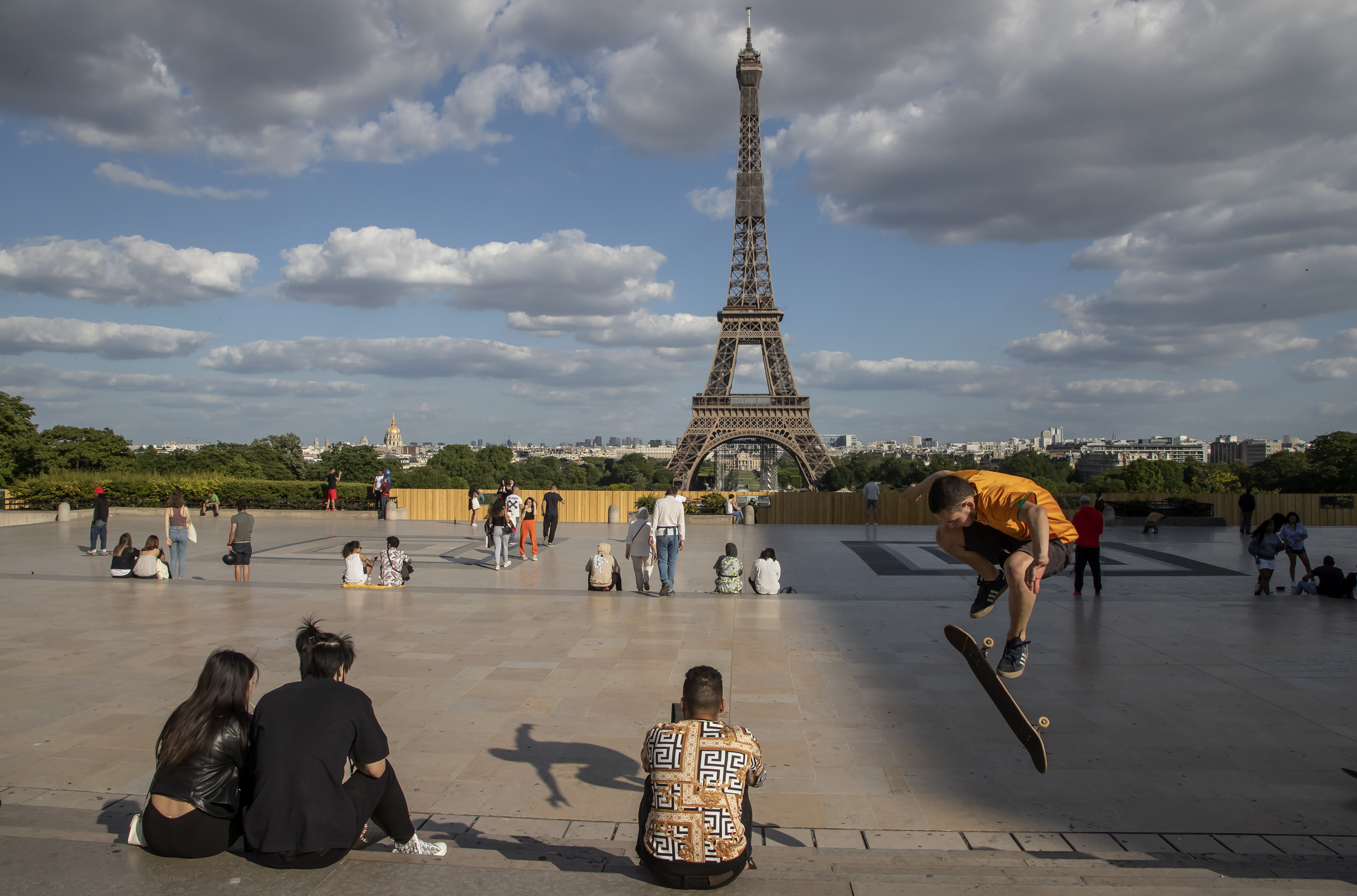 People stroll at Trocadero square near the Eiffel Tower in Paris, Monday, May 25, 2020, as France gradually lifts its Covid-19 lockdown.