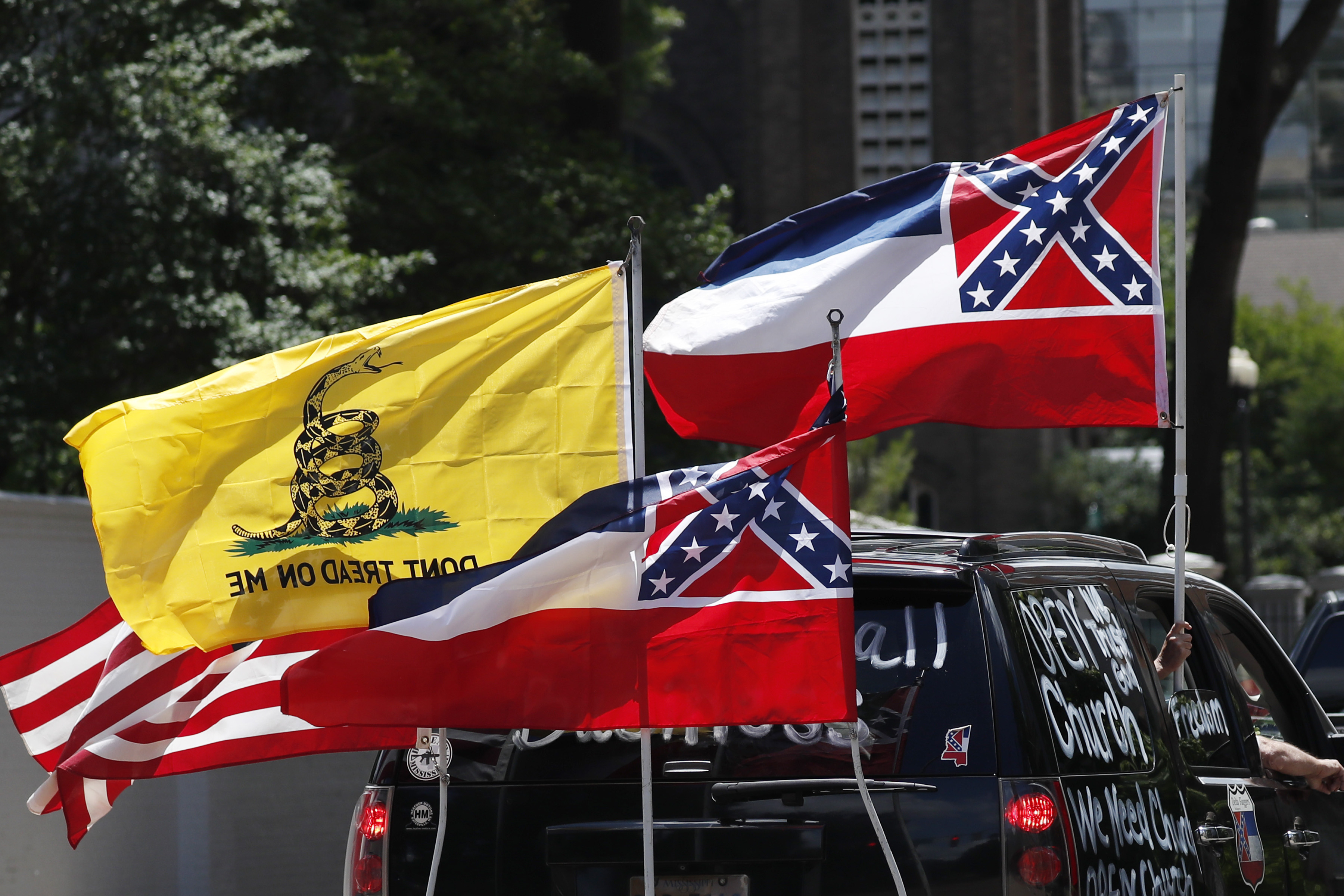 Mississippi state flags are positioned on a vehicle amid an arrangement with the American flag and a Gadsden flag during a drive-by  re-open Mississippi  protest past the Governor's Mansion, in Jackson, Miss., on April 25, 2020.